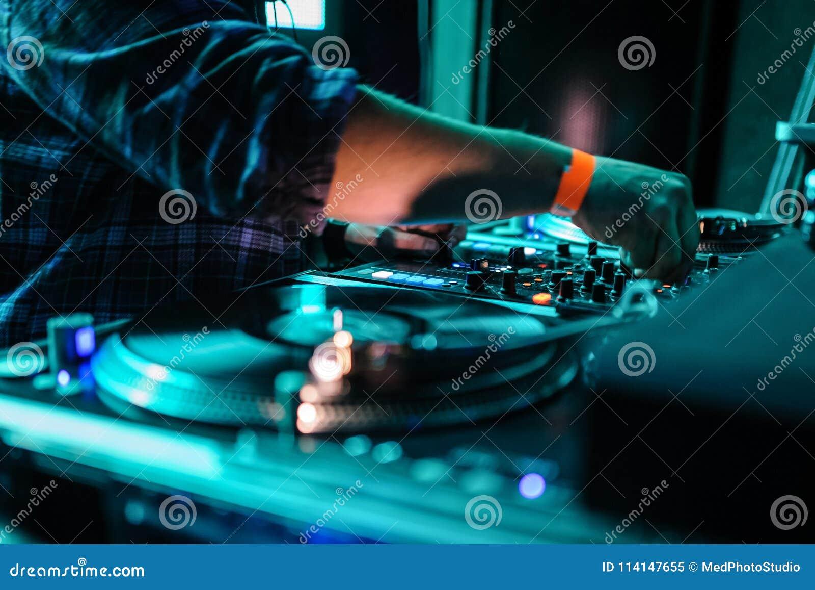 Cierre para arriba del panel de control de DJ que juega música del partido en playe moderno