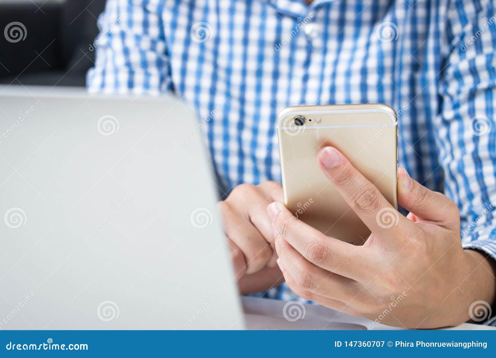 Cierre para arriba El hombre que lleva las camisas azules está utilizando los teléfonos para las compras en línea
