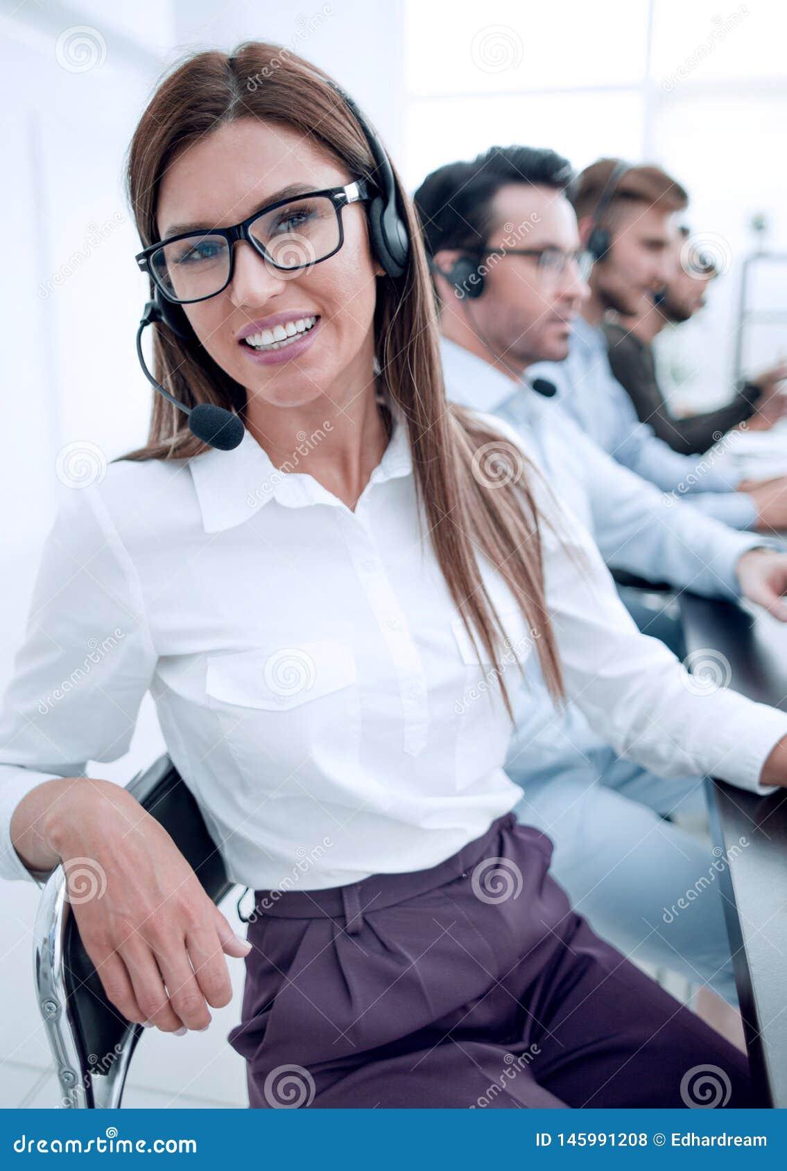 Cierre para arriba empleado del centro de atenci?n telef?nica que se sienta en su escritorio