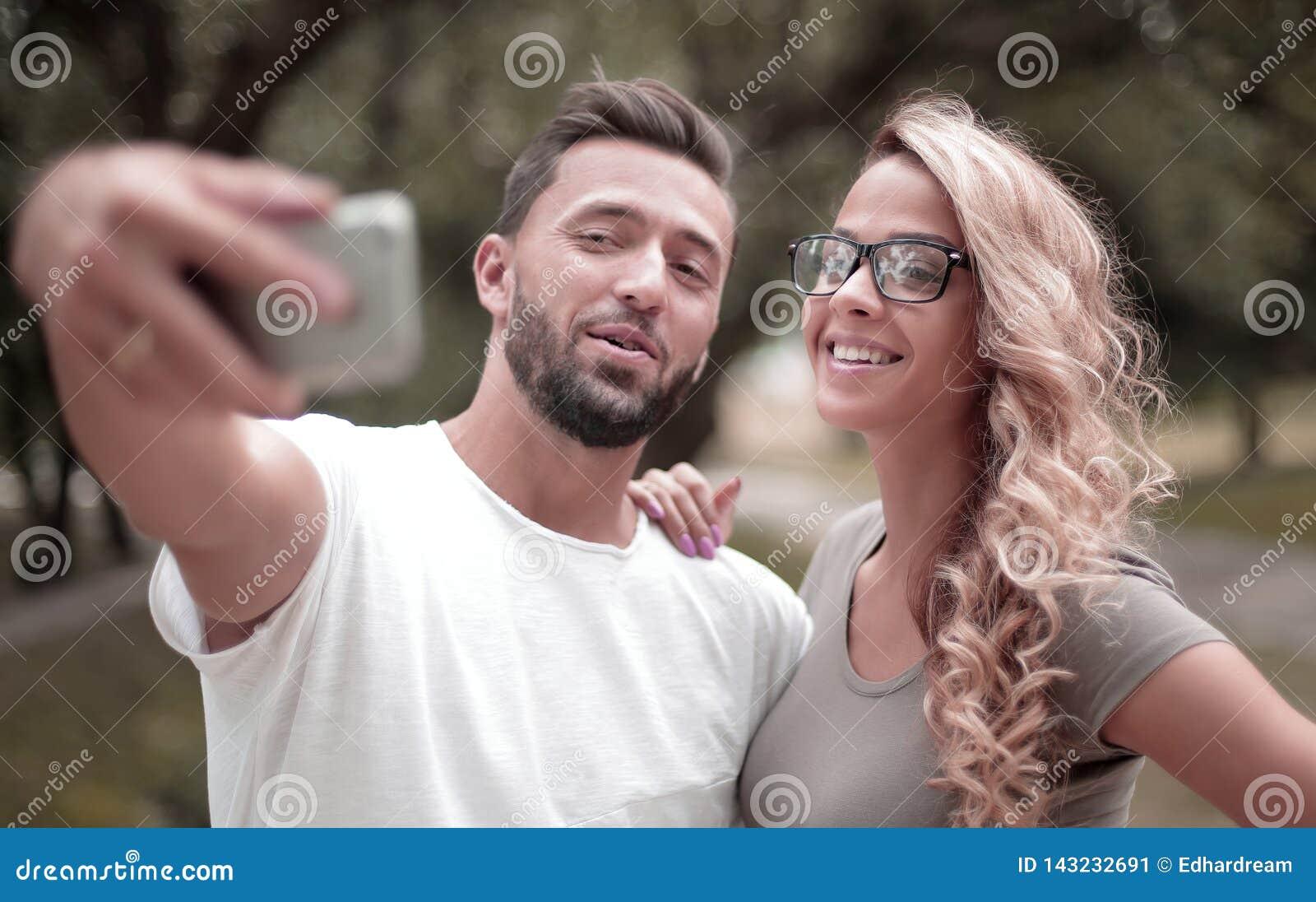Cierre para arriba pares jovenes sonrientes que toman el selfie en parque de la ciudad