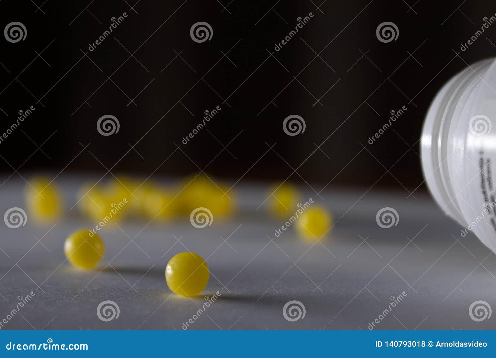 Cierre suave del foco para arriba tirado de una sola píldora amarilla mientras que muchos otros se empañan en el fondo