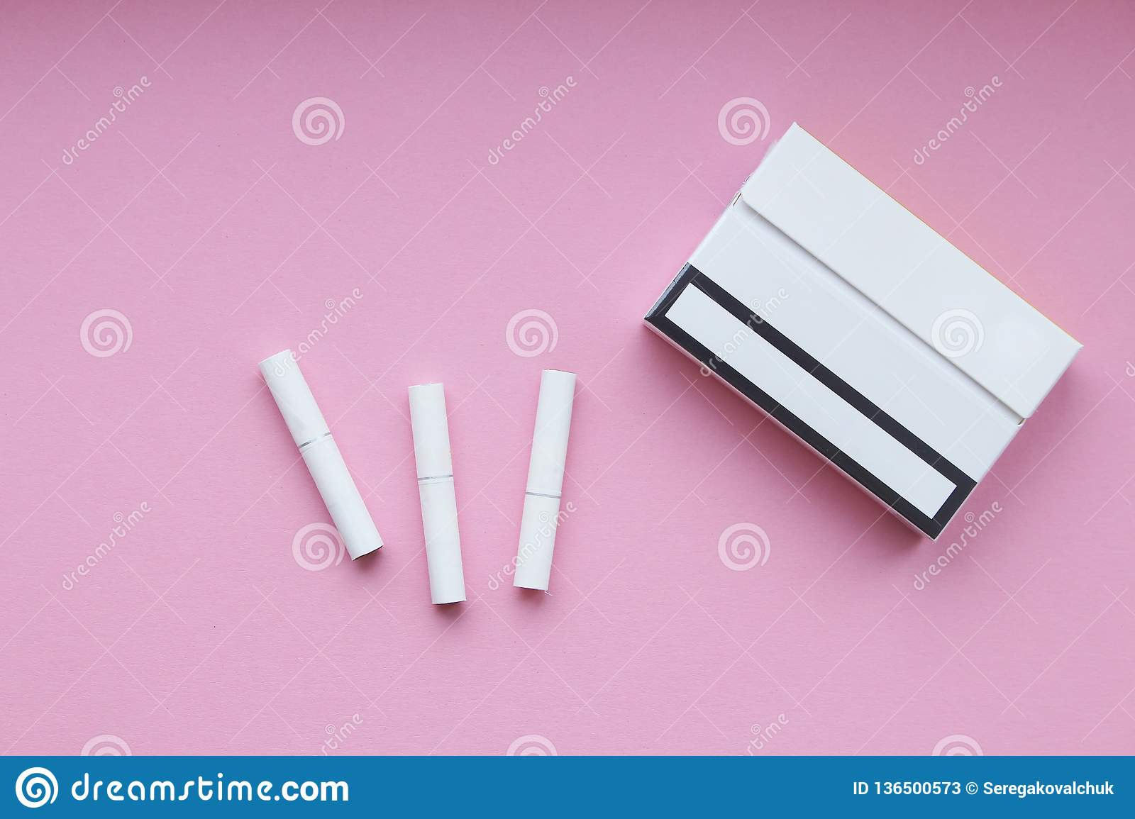 Cigarette sticks and pack on pink background