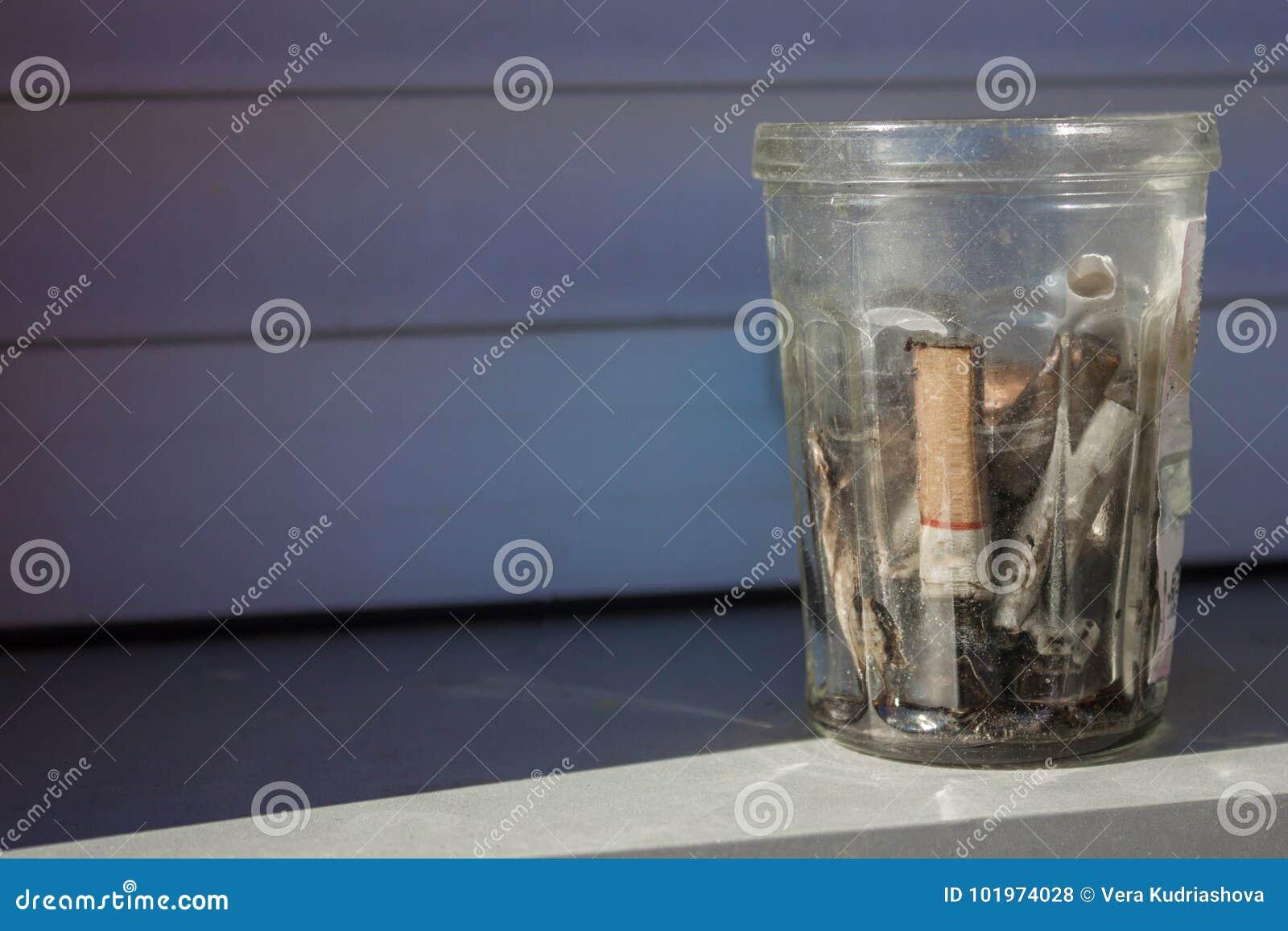 Cigarettstumpar i ett smutsigt exponeringsglas