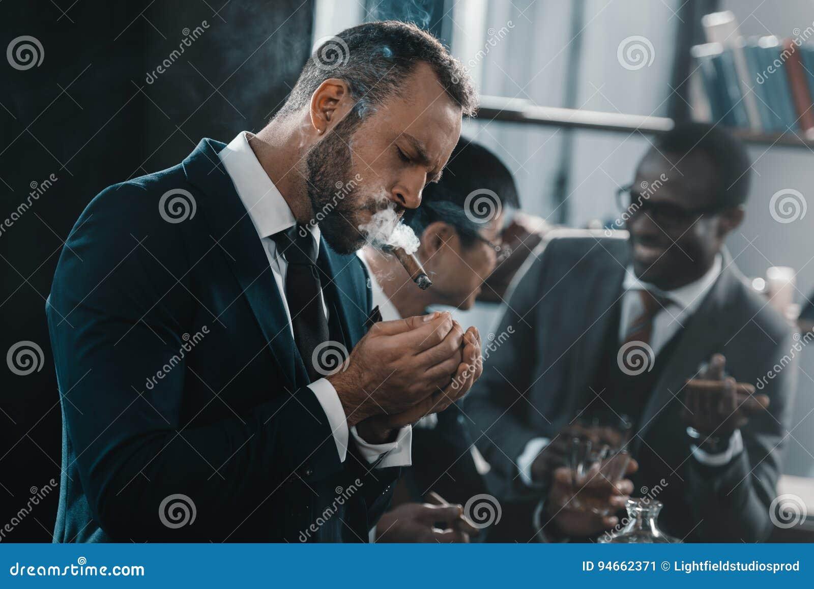 Cigarro que fuma del hombre de negocios con el equipo multicultural del negocio