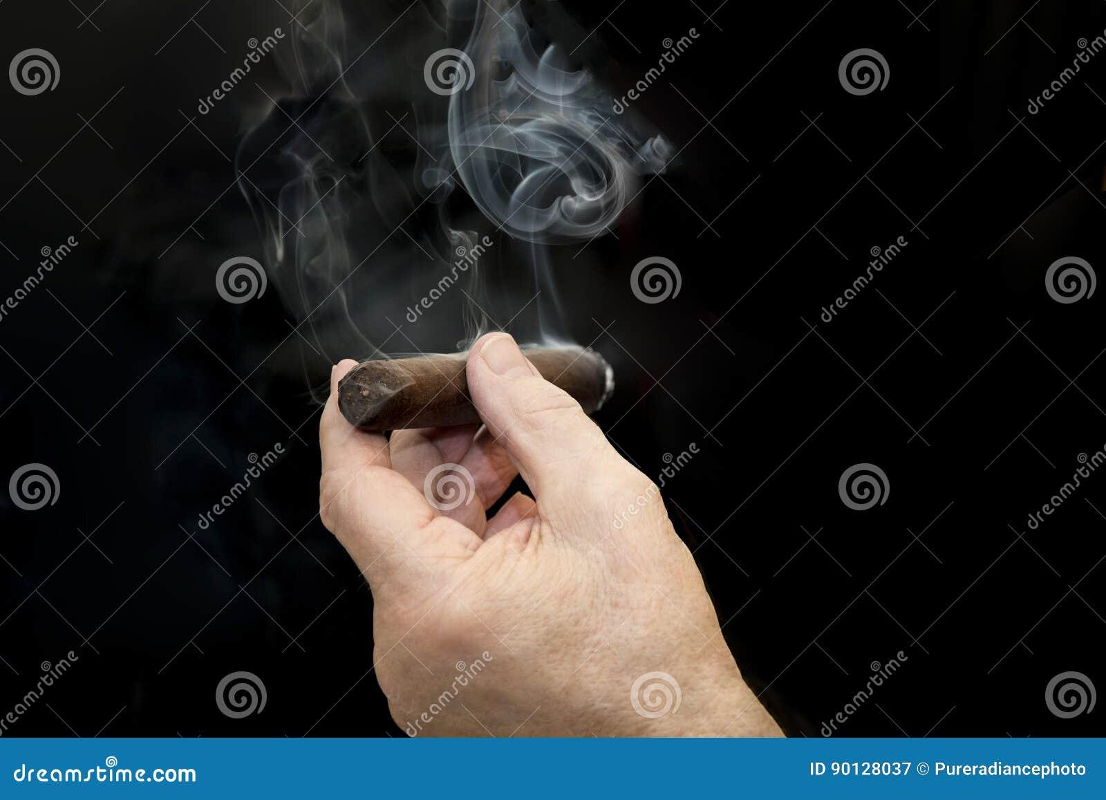 Cigarro y mano con humo