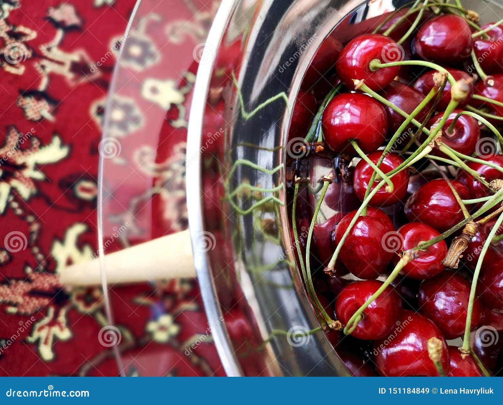Ciliege mature dolci in un di piastra metallica su una tavola di vetro