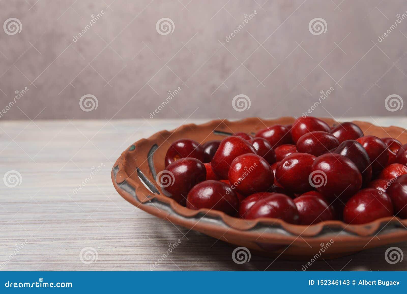 Ciliegie rosse in un piatto dell argilla su una tavola di legno bianca
