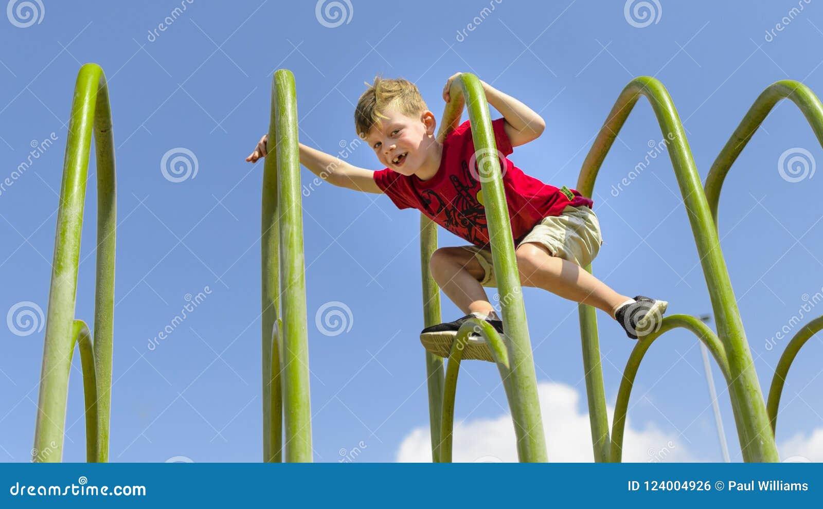 Cimbing在playframe的勇敢的年轻男孩
