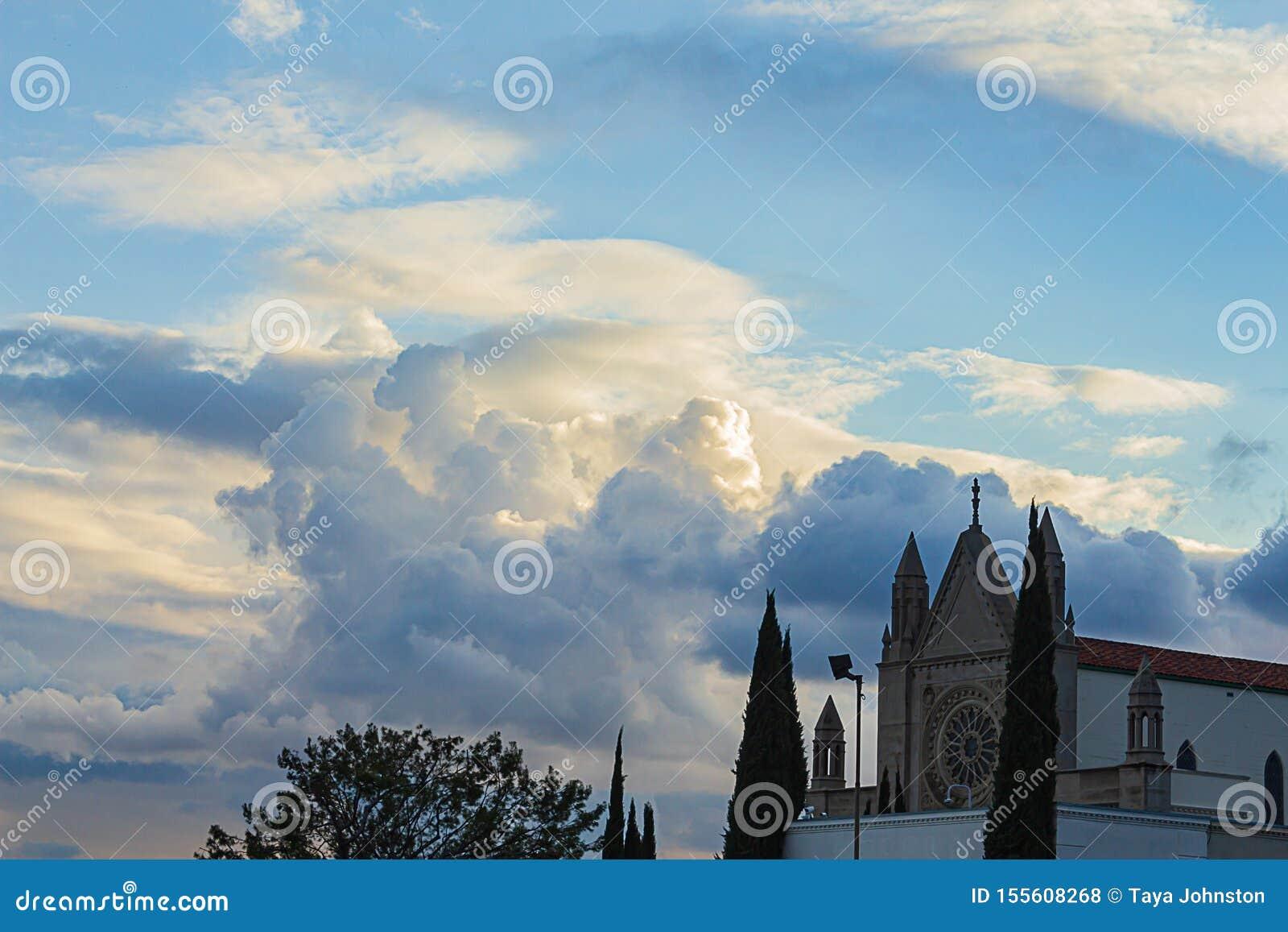 Cime della costruzione e dell albero di chiesa con le nuvole di nimbus billowing maestose del cumulo