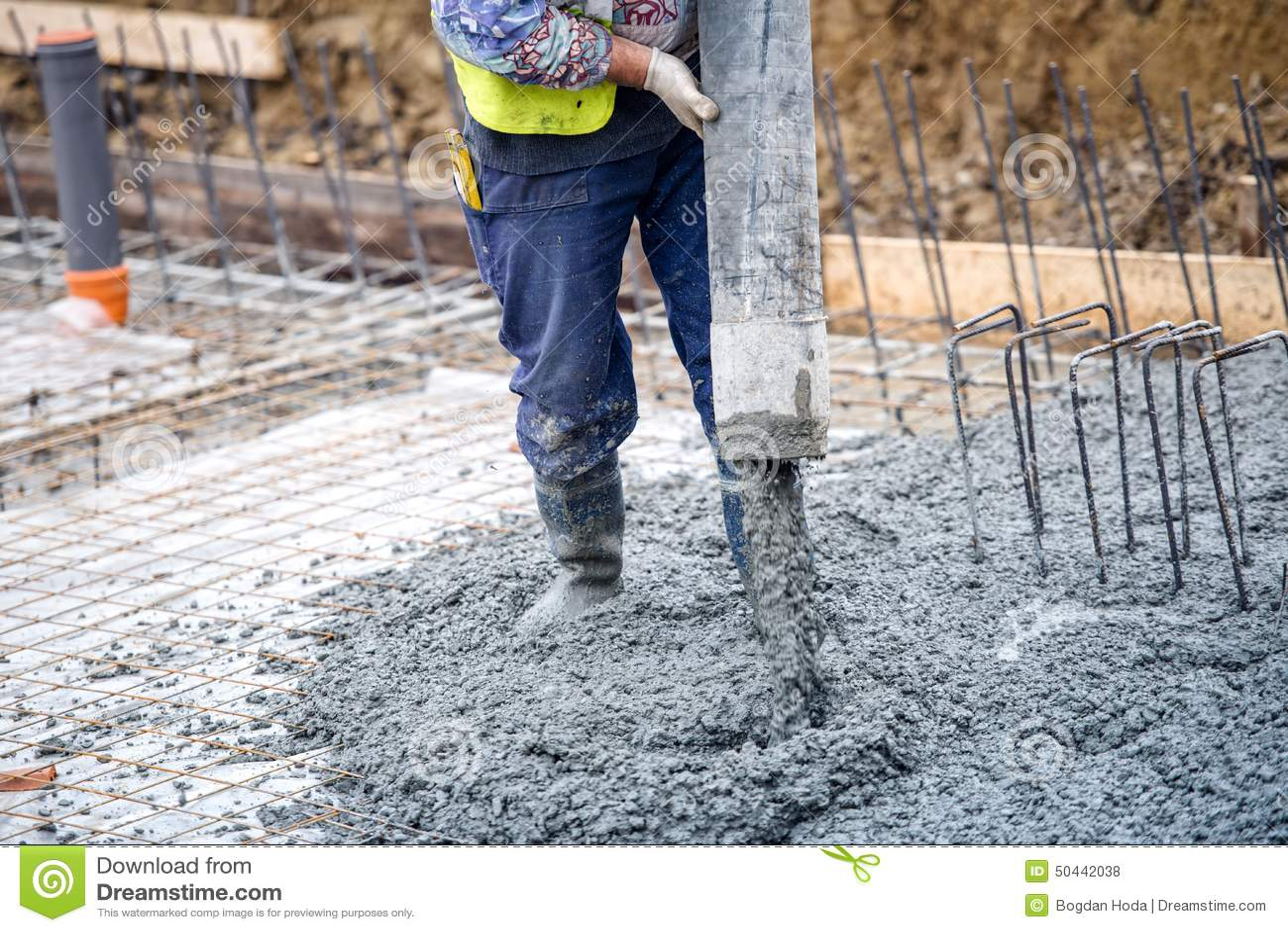 Cimento ou concreto de derramamento do trabalhador de construção civil com tubo de bomba