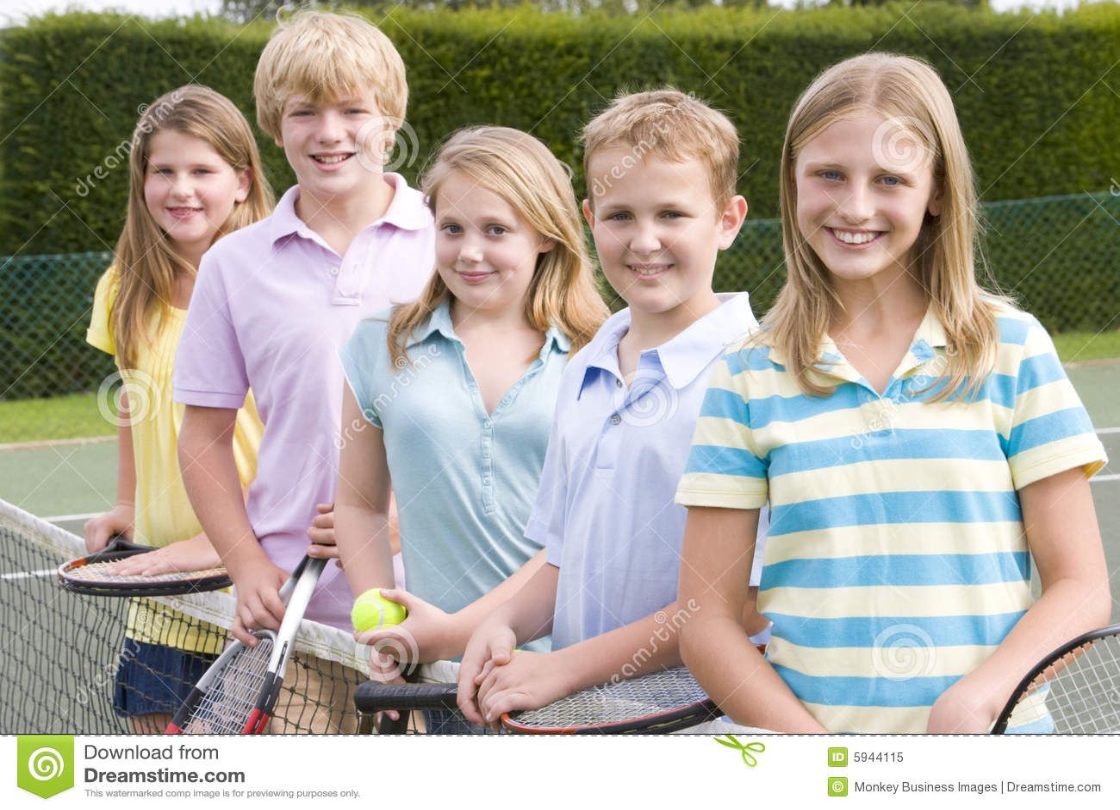 Cinco amigos jovenes en campo de tenis