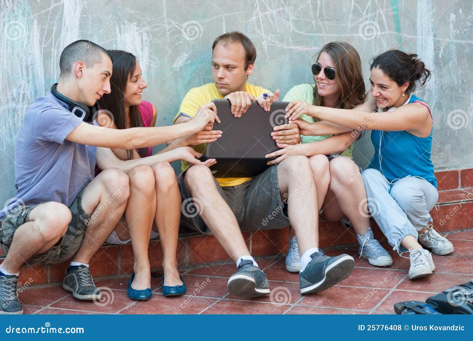 Cinco amigos que lutam sobre um portátil