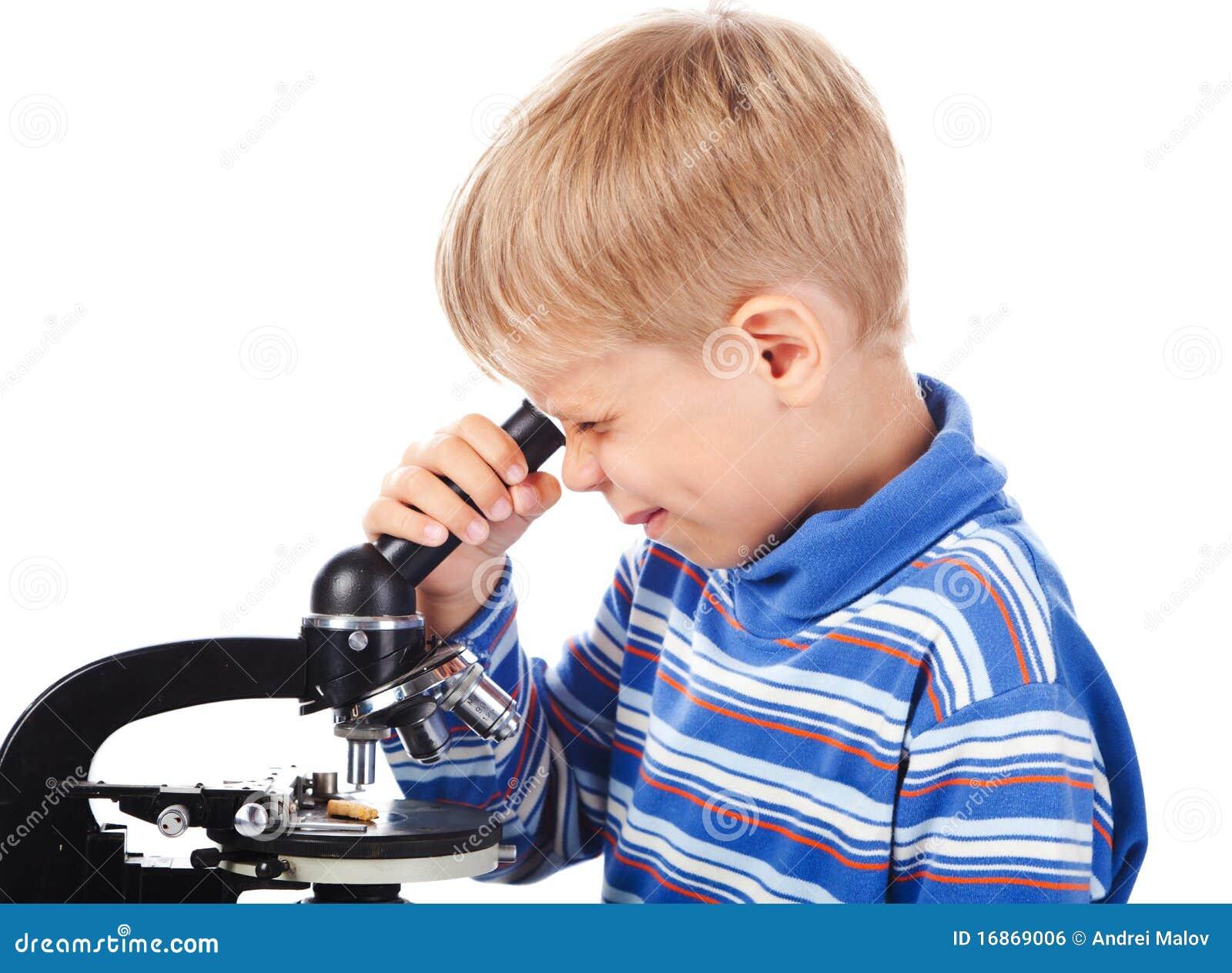 Cinco anos de menino idoso com microscópio