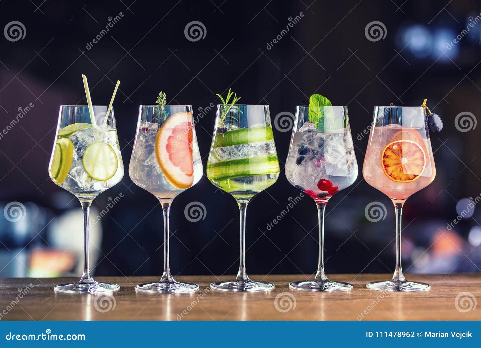 Cinco cocktail coloridos do tônico da gim em vidros de vinho no contador da barra