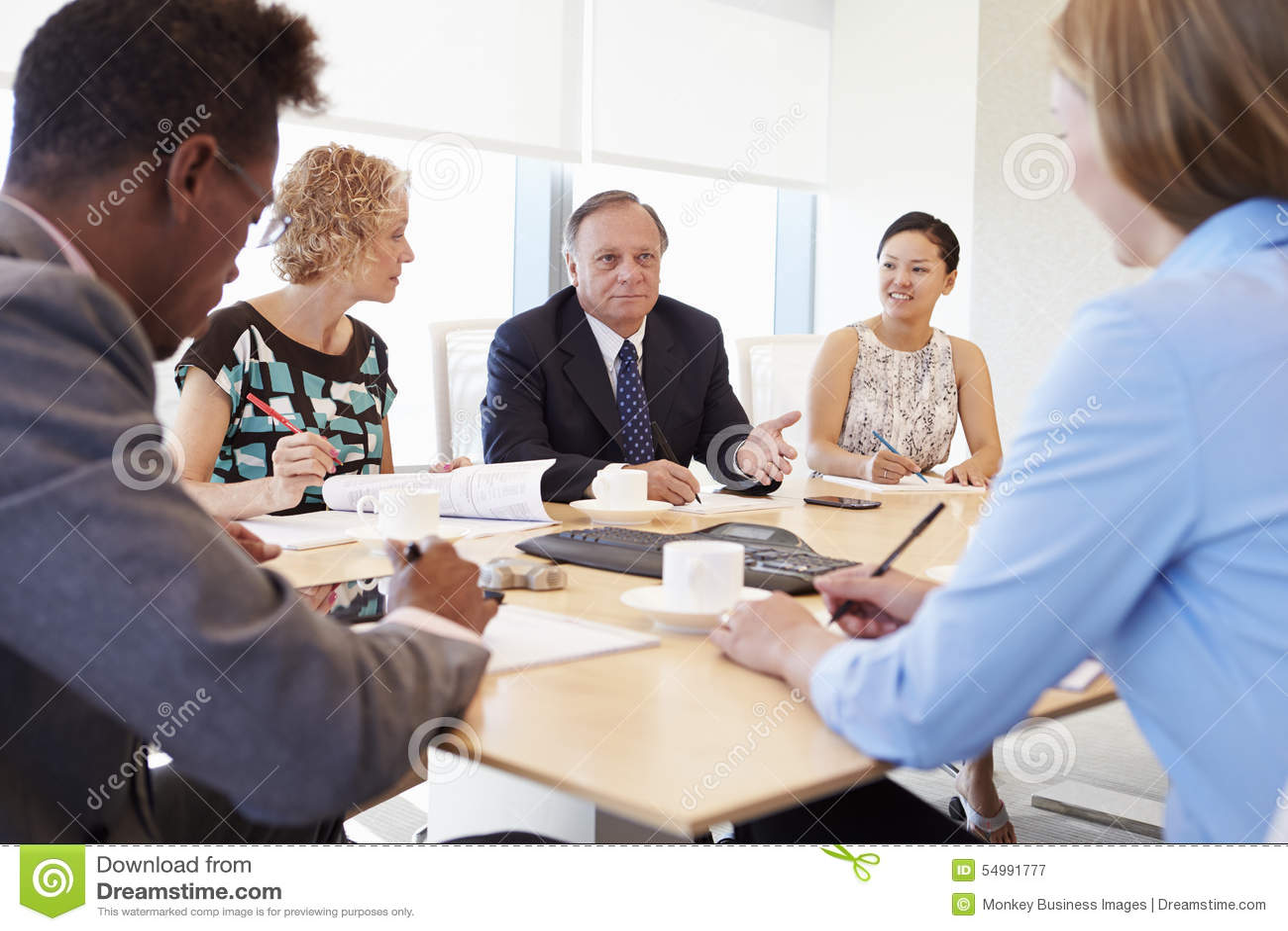 Cinco empresarios que tienen reunión en la sala de reunión