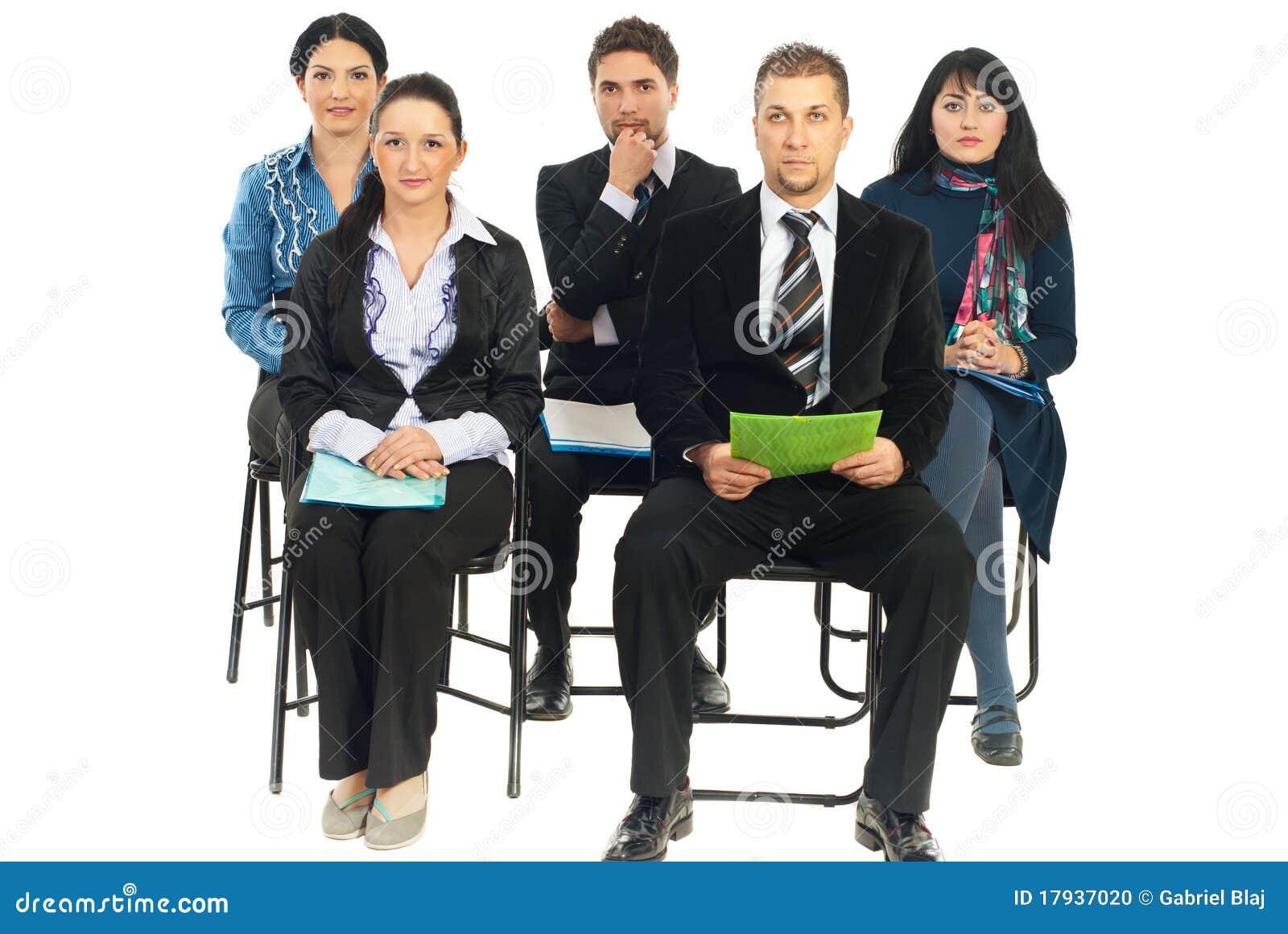 Cinco hombres de negocios que escuchan en la conferencia