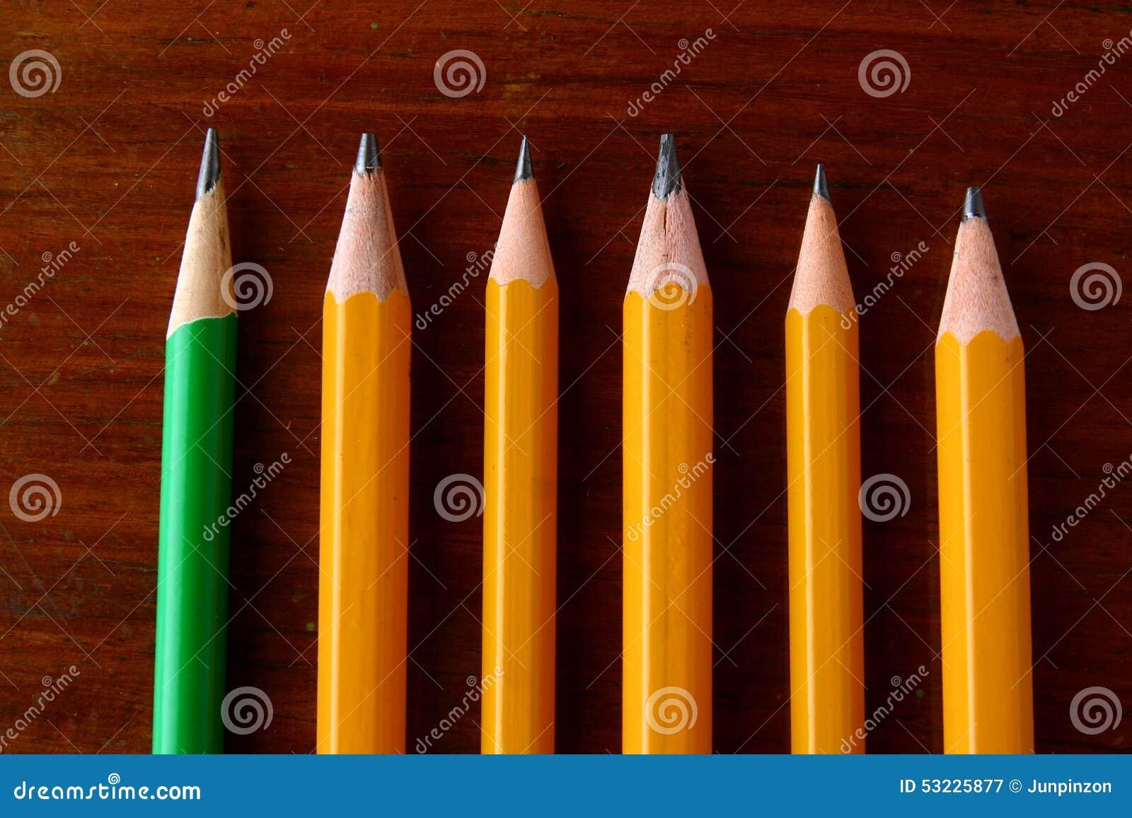 Cinco lápices amarillos y un lápiz verde