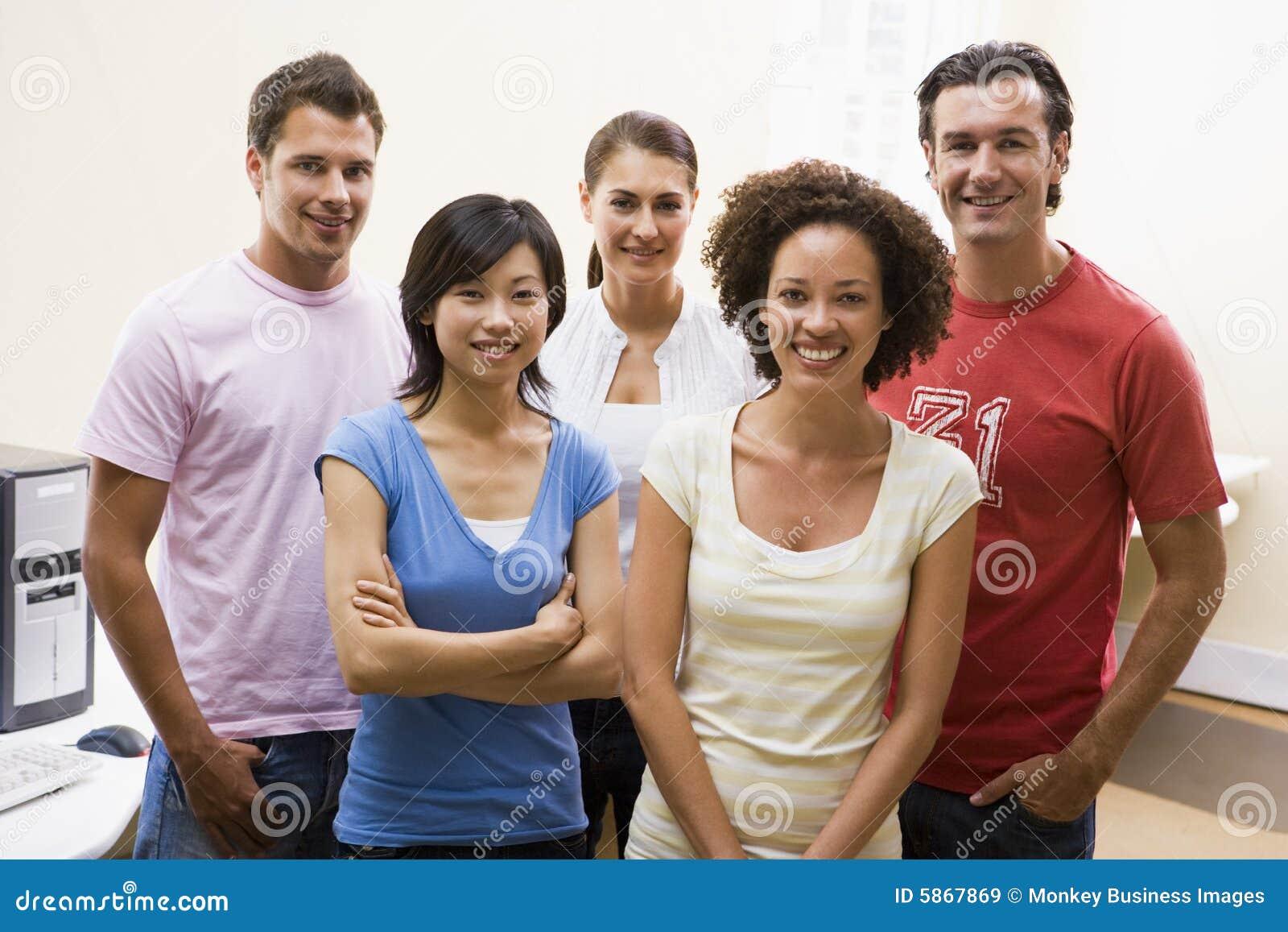 Cinco personas que se colocan en la sonrisa de la sala de ordenadores