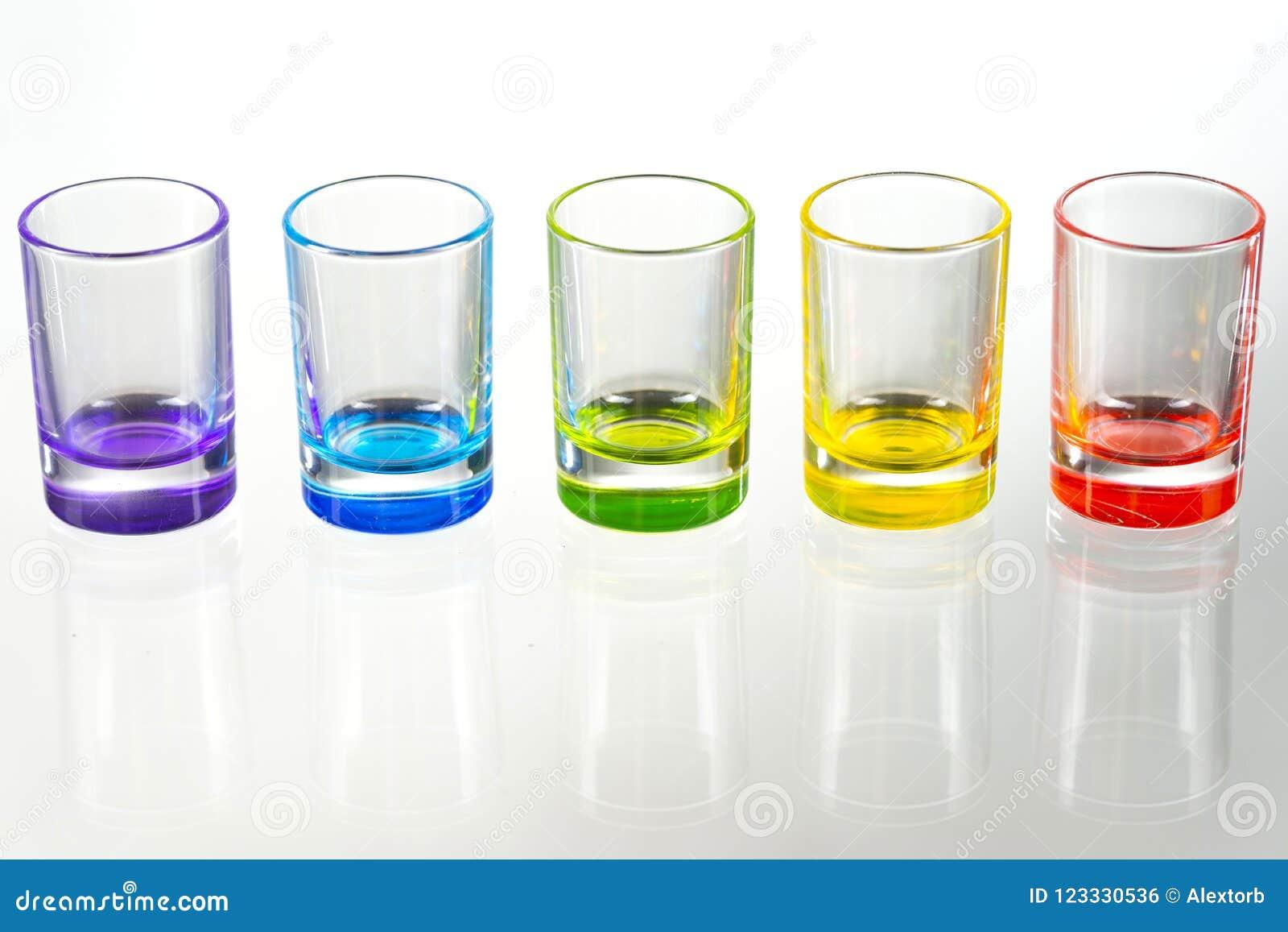 Cinco vasos de medida vacíos multicolores colocados simétricamente en un w