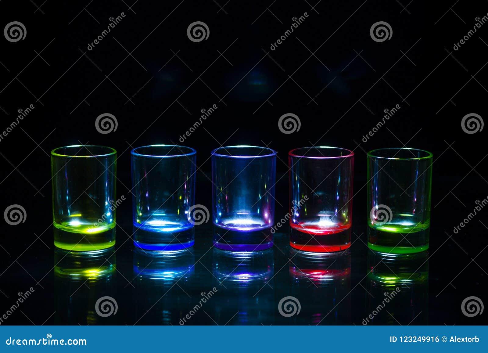 Cinco vasos de medida vacíos multicolores que reflejan en un surfa de cristal