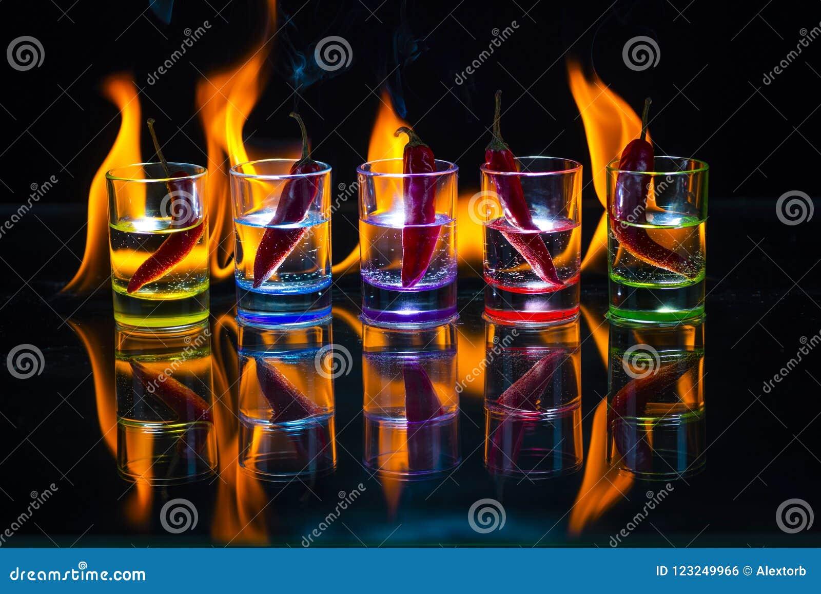 Cinco vidros de tiro coloridos completamente da bebida e com o ch vermelho