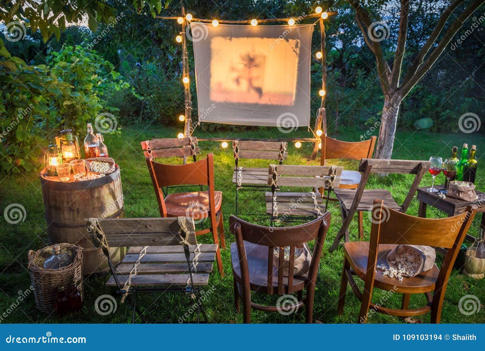 Cinema do verão com o projetor retro no jardim
