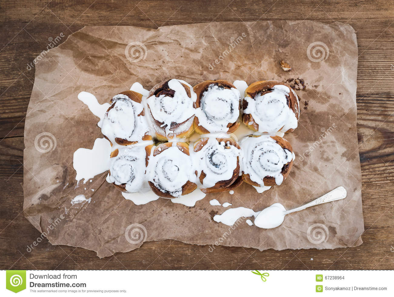 Cinnamon rolls with cream cheese icing on piece of oily craft royalty free stock photo jeuxipadfo Choice Image