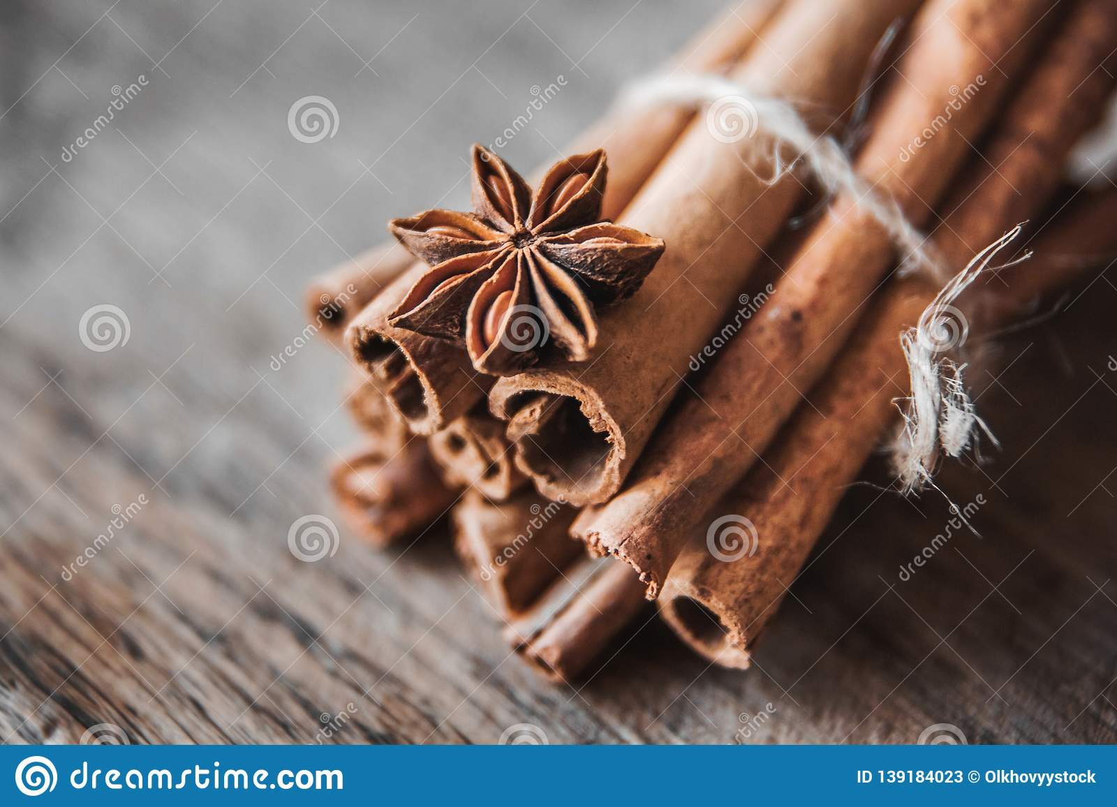 Cinnamon sticks and aniseon on the wooden surface.