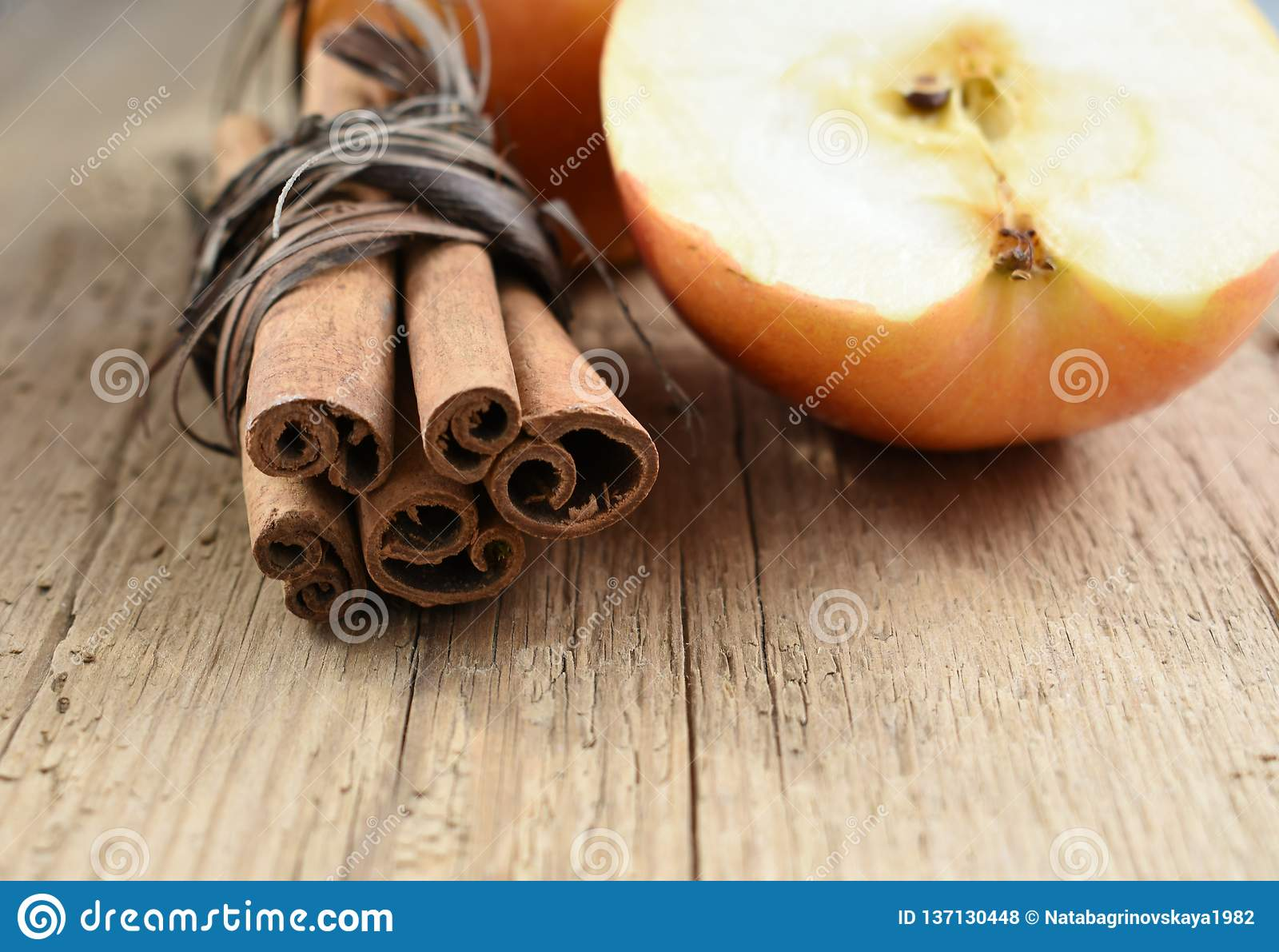 Cinnamon sticks and apple on wooden table ingredient