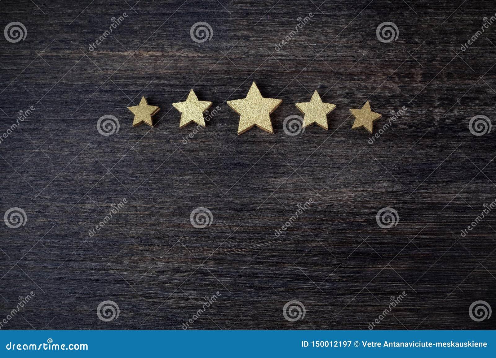 Cinq étoiles d or sur le fond en bois, concept de évaluation supérieur