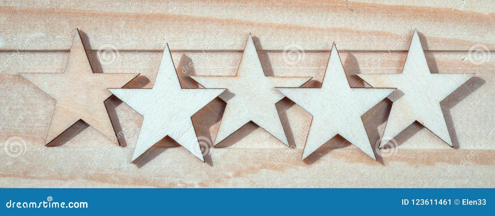 Cinq étoiles en bois sur un fond en bois
