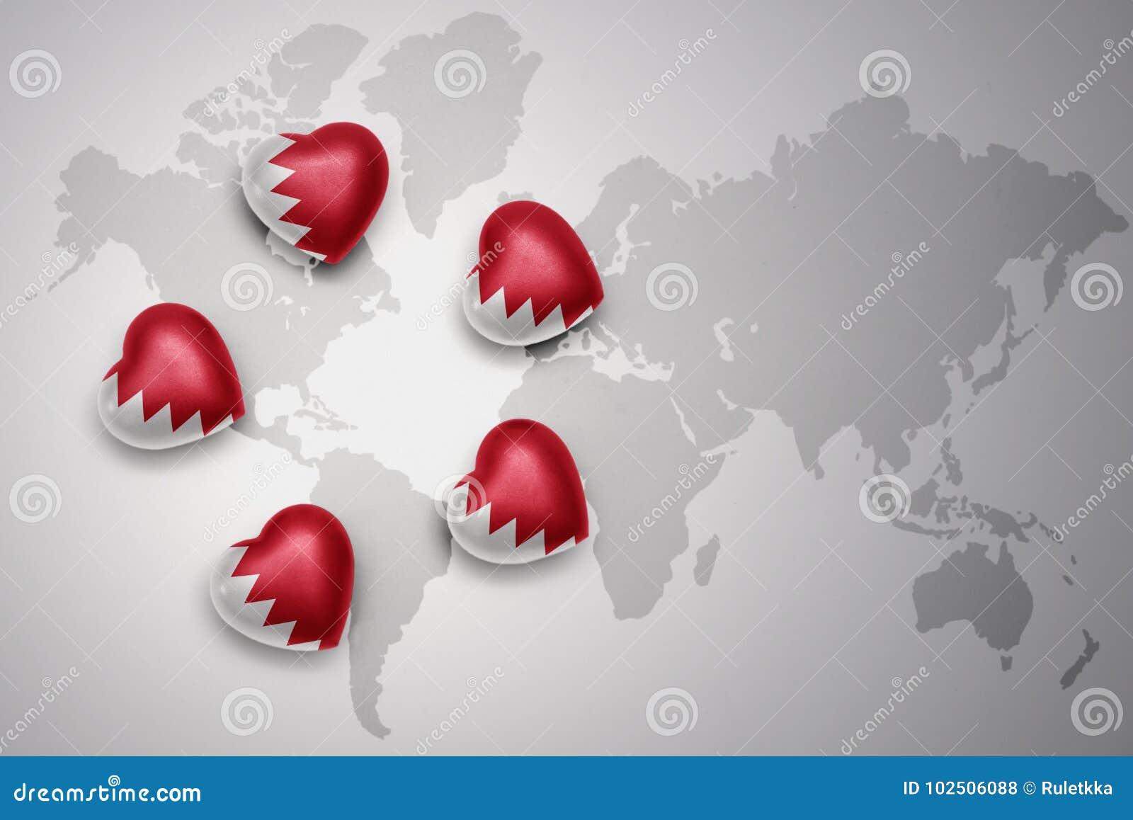 Cinq coeurs avec le drapeau national du Bahrain sur un fond de carte du monde