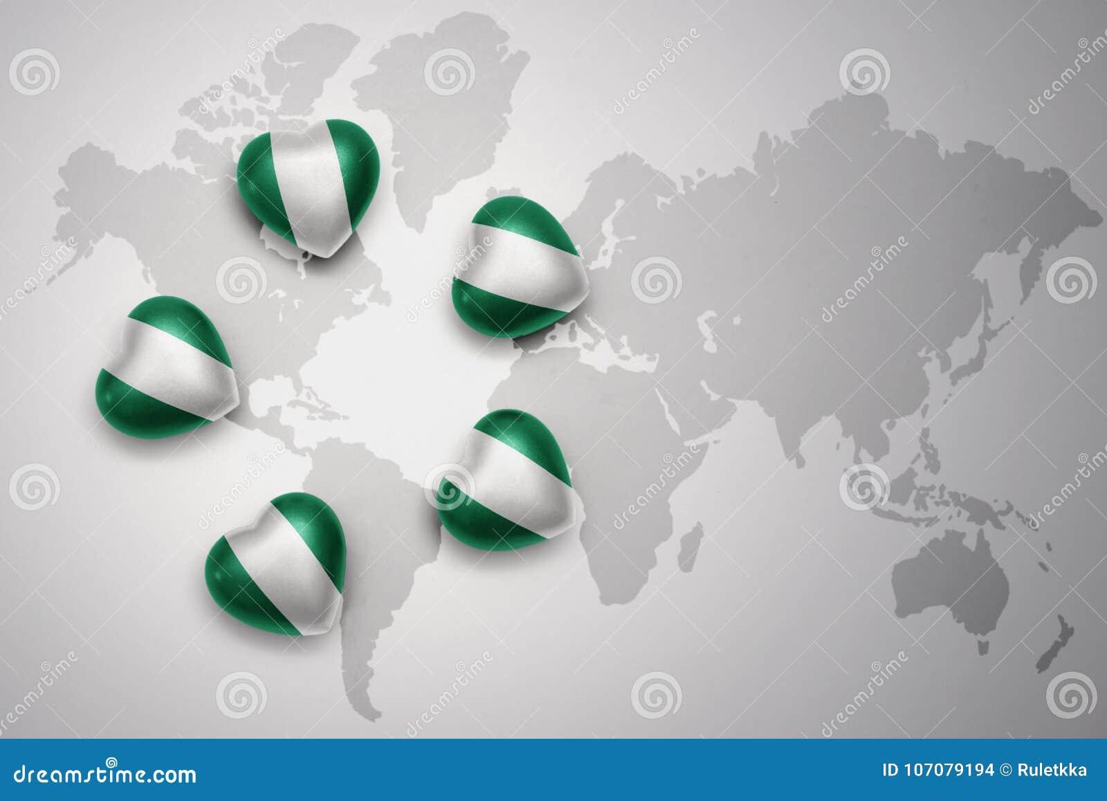 Cinq coeurs avec le drapeau national du Nigéria sur un fond de carte du monde