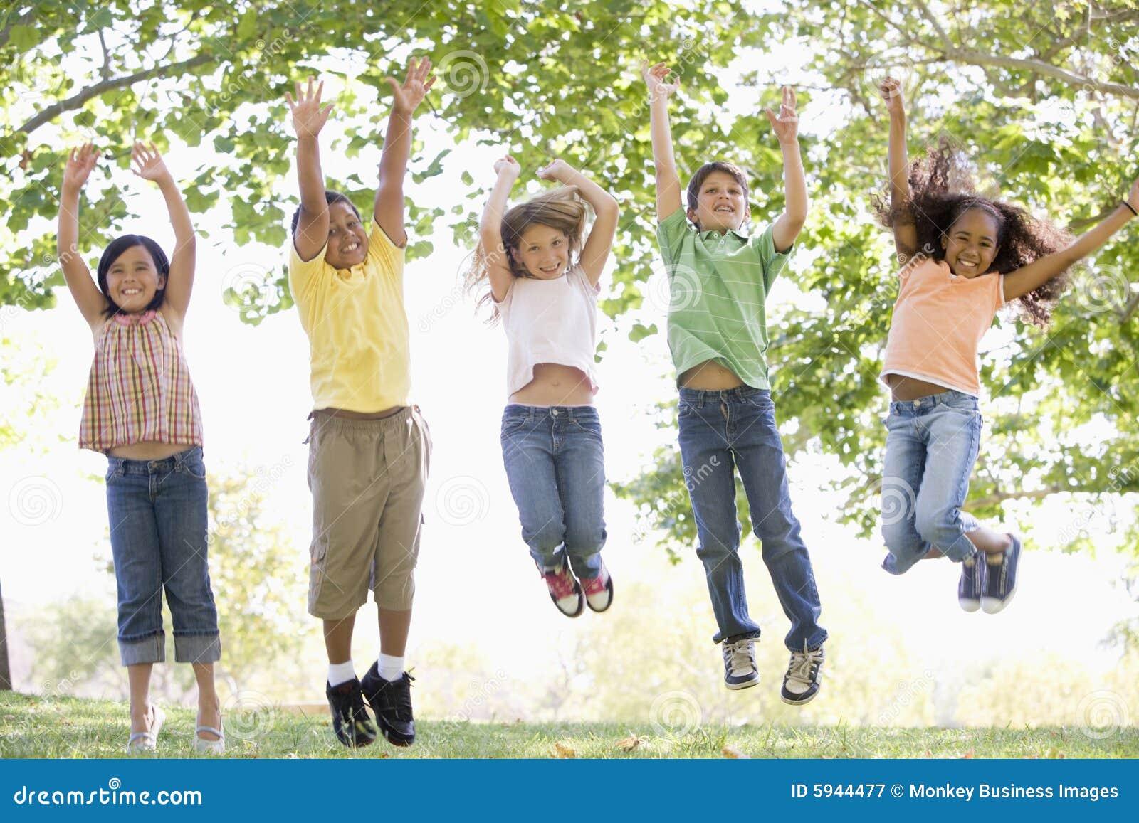 Cinq jeunes amis branchant à l extérieur le sourire