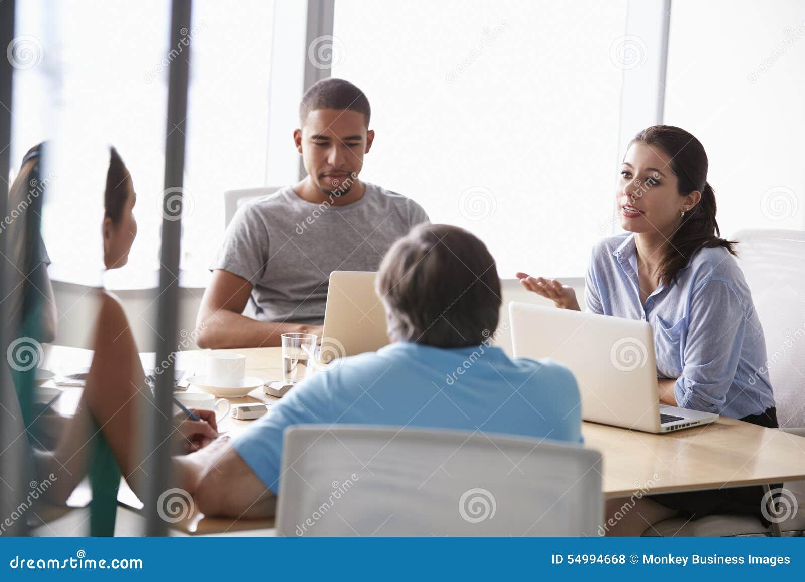Cinque persone di affari che hanno riunione in sala del consiglio
