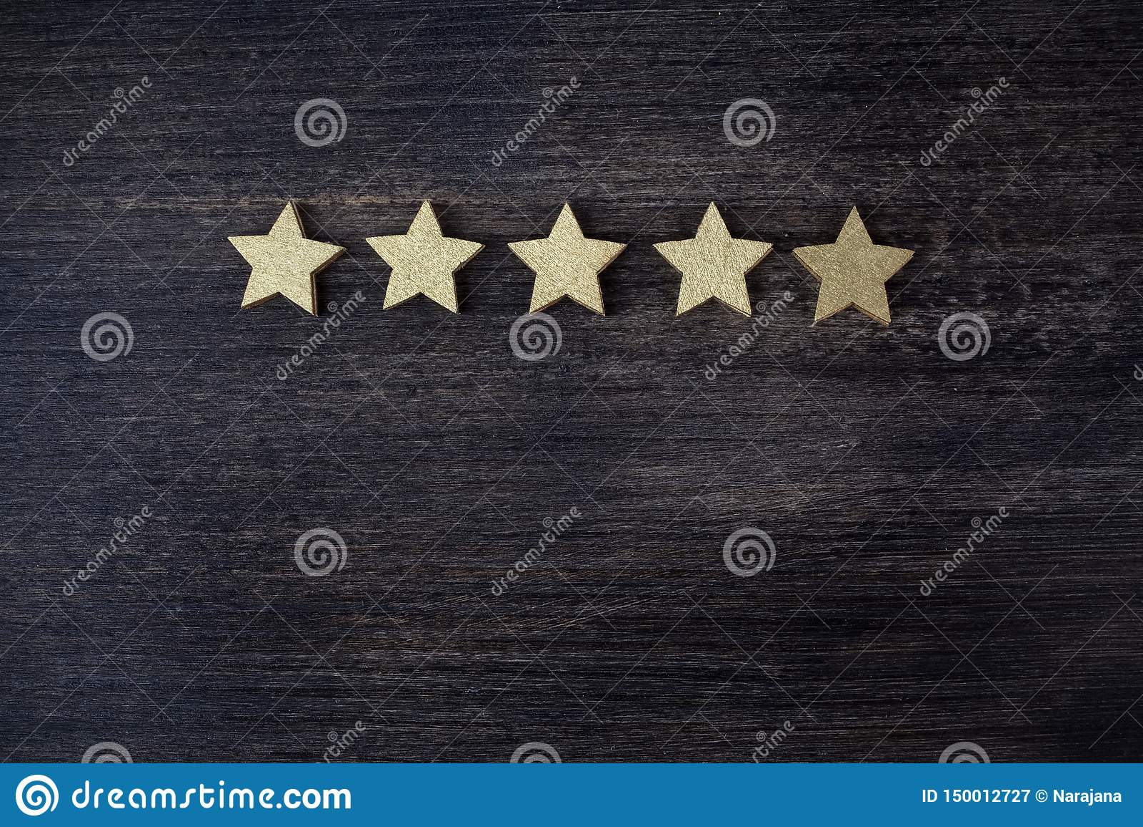 Cinque stelle dorate su fondo di legno, concetto di valutazione superiore