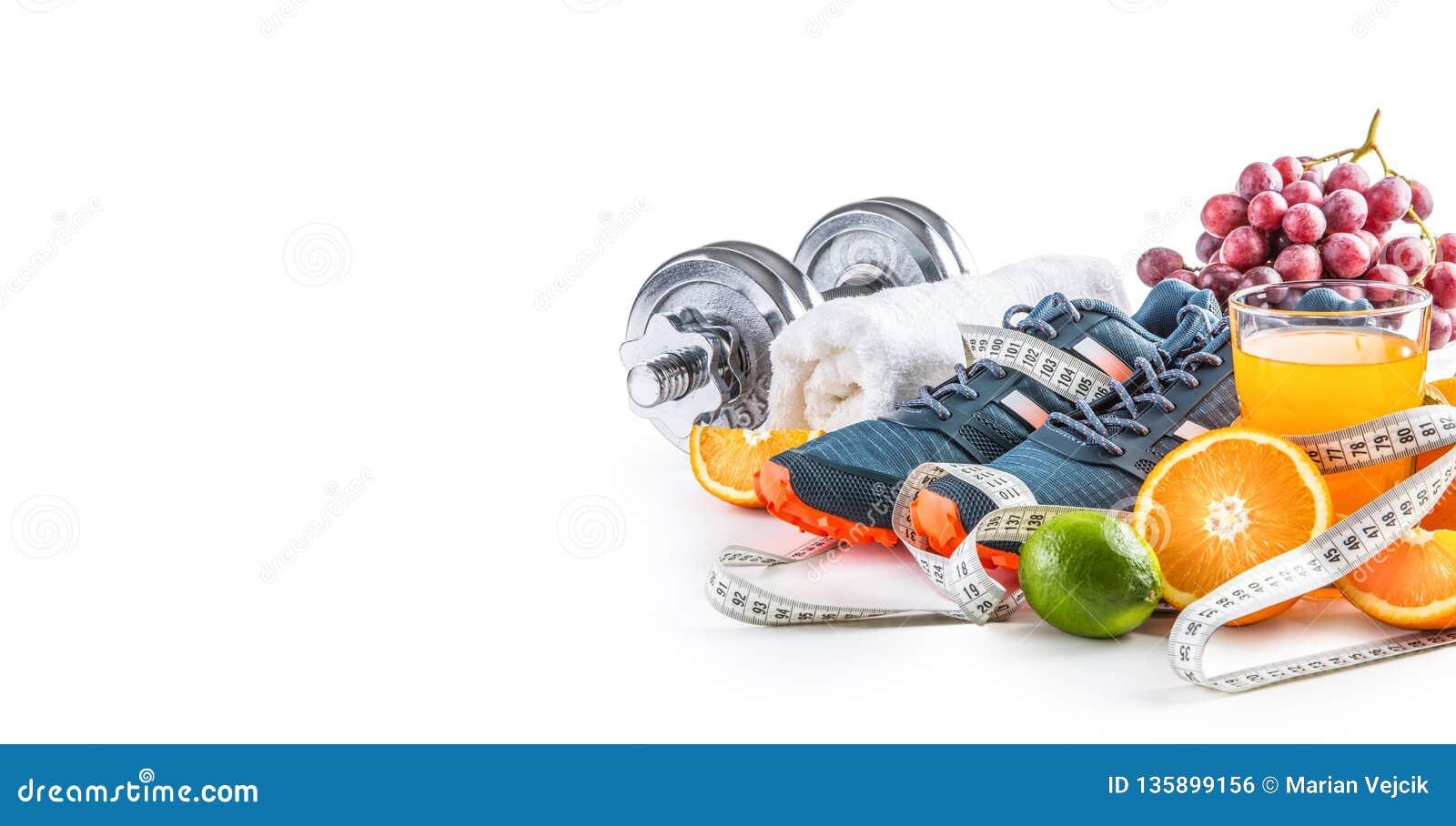 Cinta de la medida de la fruta fresca de las pesas de gimnasia de los zapatos del deporte y jugo del multivitamin aislado en el f