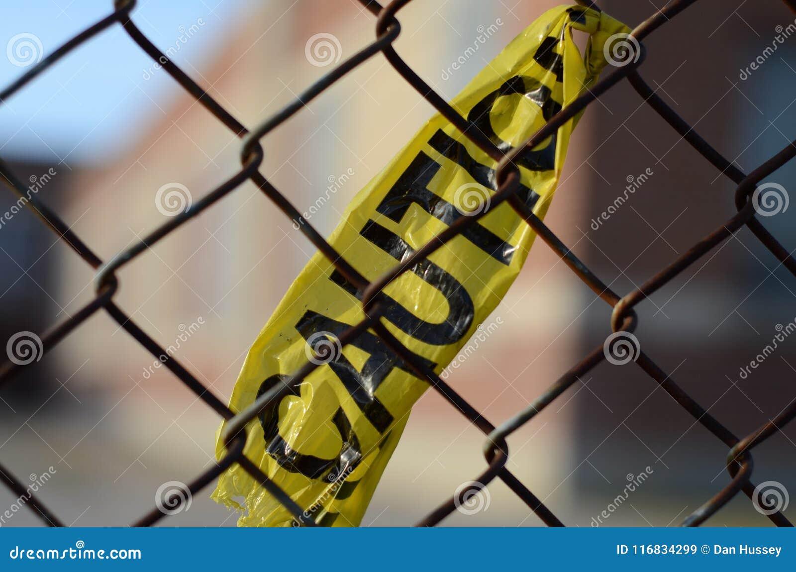 Cinta de la precaución atada a una cerca de la alambrada