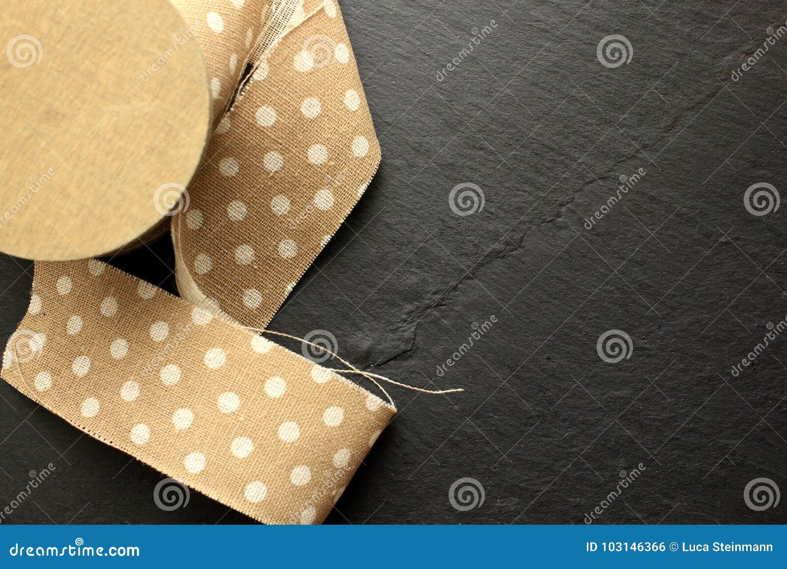 Cinta del algodón en el rollo de madera en fondo negro