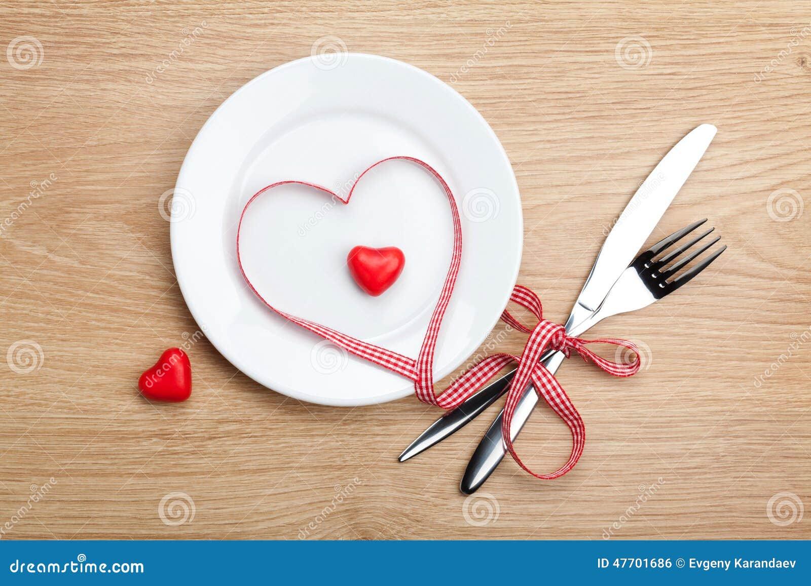 Cinta roja en forma de corazón del día de tarjeta del día de San Valentín sobre la placa con silverwa
