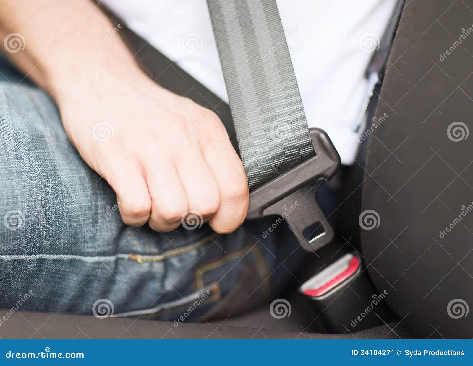 Cinto de segurança da asseguração do homem no carro