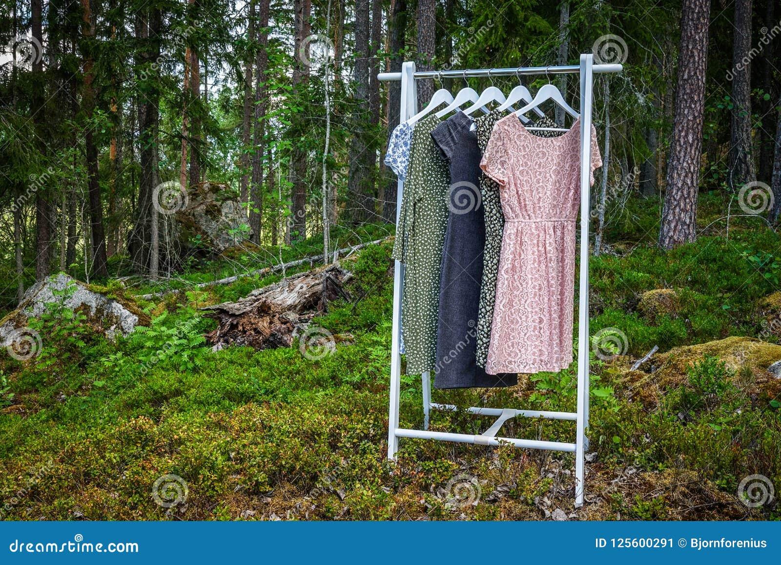 Cintre avec des robes dans les bois