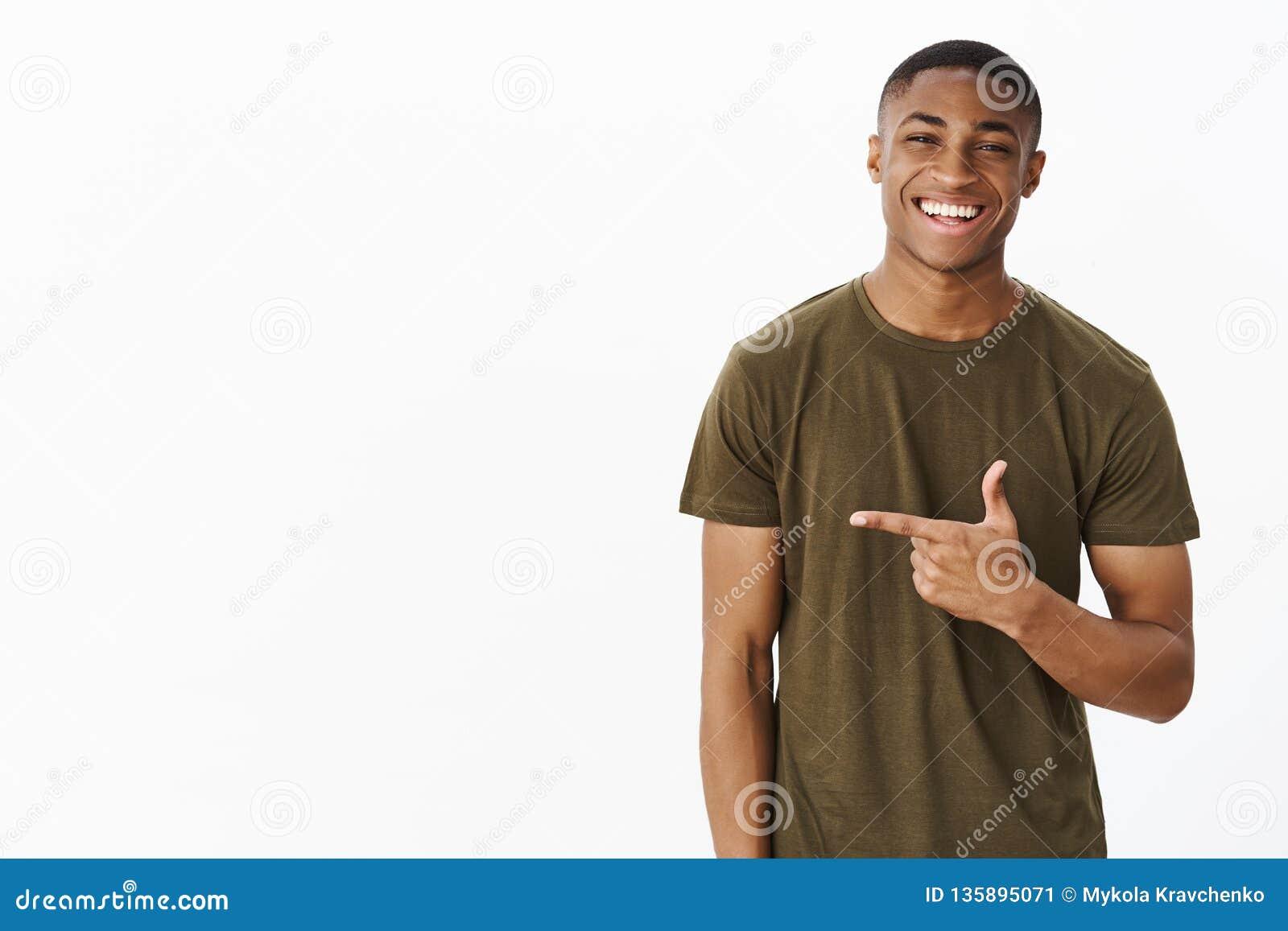 Cintura-acima disparada do homem afro-americano novo agradável e considerável alegre que aponta a esquerda com o indicador que so