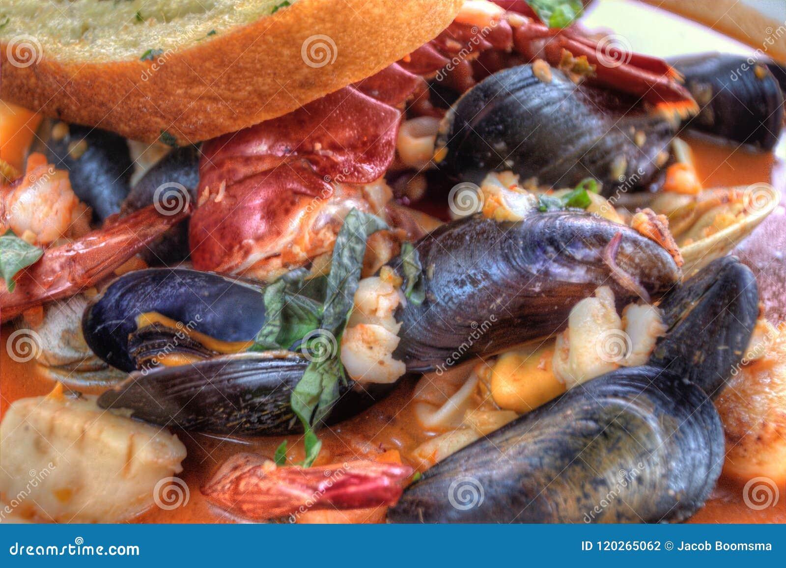 Cioppino a servi avec les mollusques et crustacés et le pain à l ail