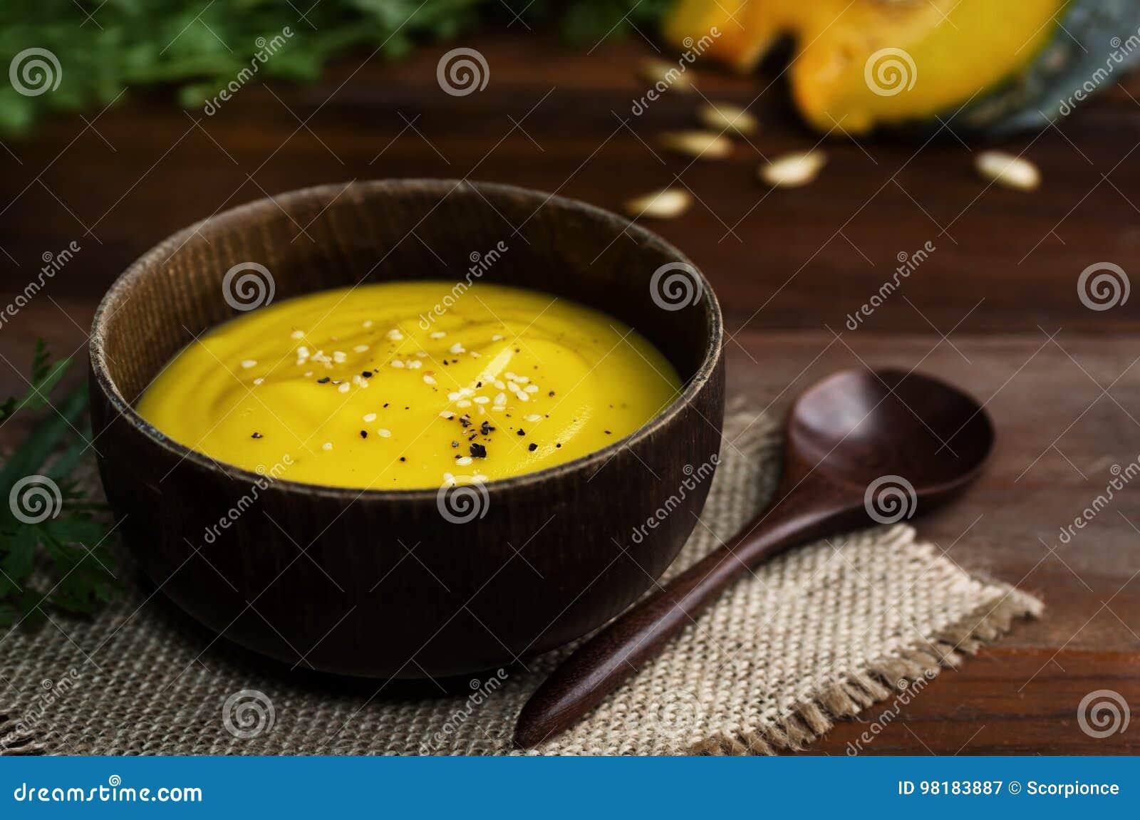 Ciotola di legno di minestra gialla vibrante della zucca con il cucchiaio sulla tavola
