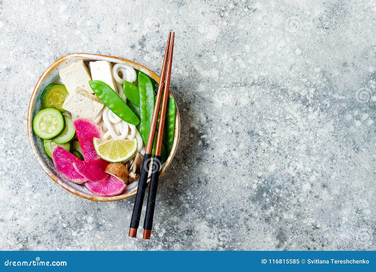 Ciotola di minestra asiatica delle tagliatelle del udon del vegano con lo zenzero ed i funghi brodo, tofu, piselli improvvisi, zu