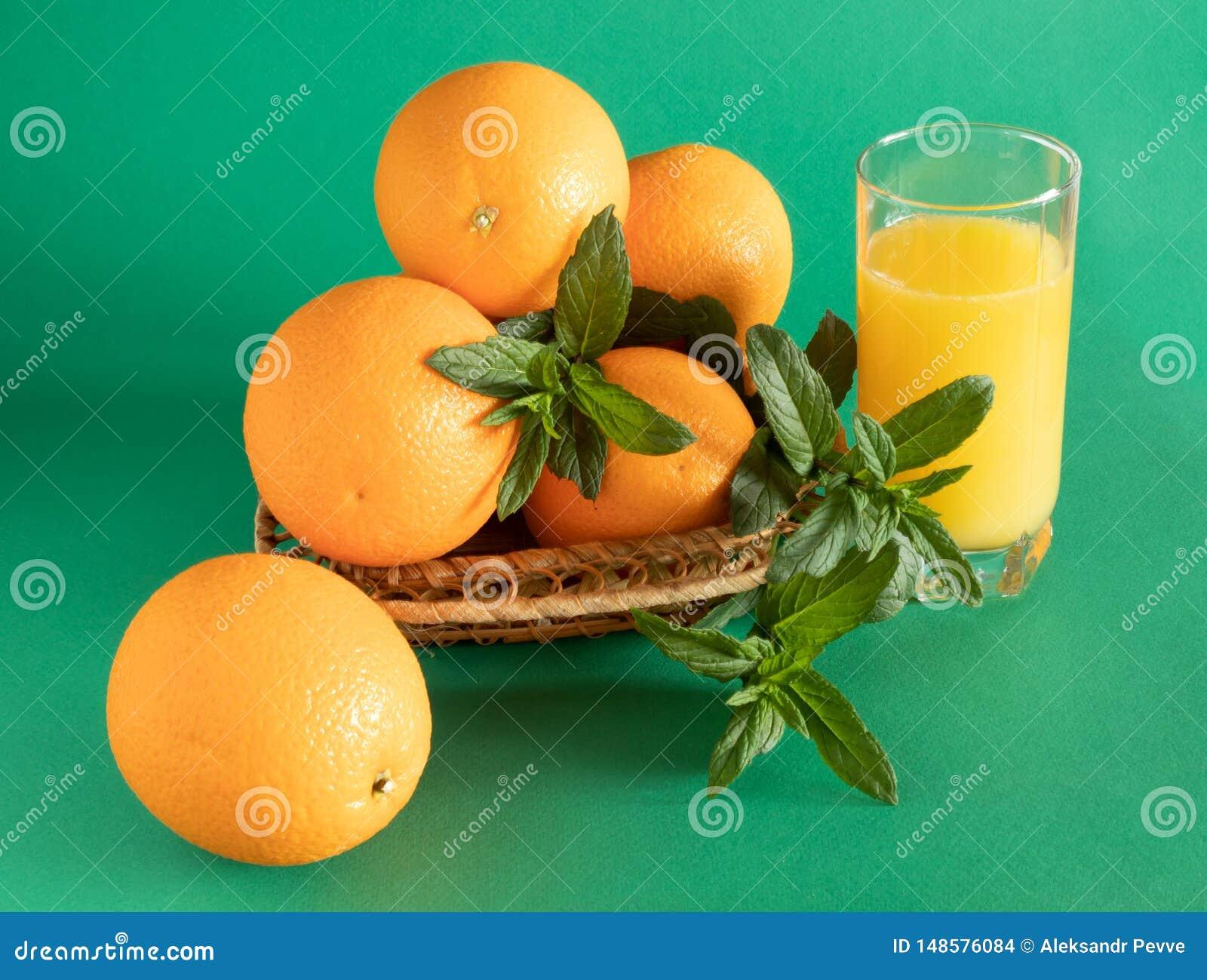 Ciotola di vimini con le arance decorate con la menta, accanto ad un vetro con succo d arancia su un fondo verde