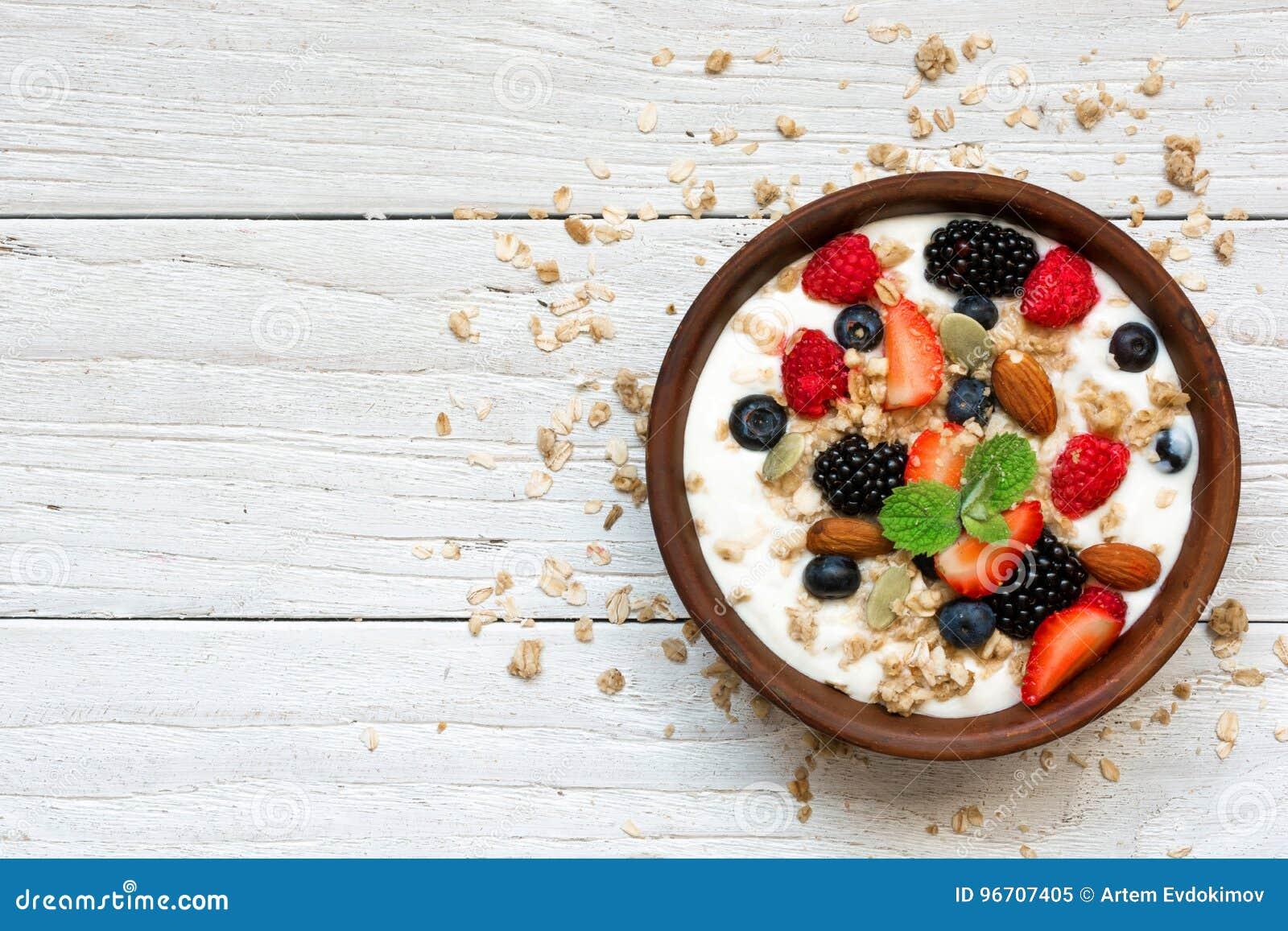 Ciotola di yogurt greco con granola, l avena, le bacche ed i dadi per la prima colazione sana