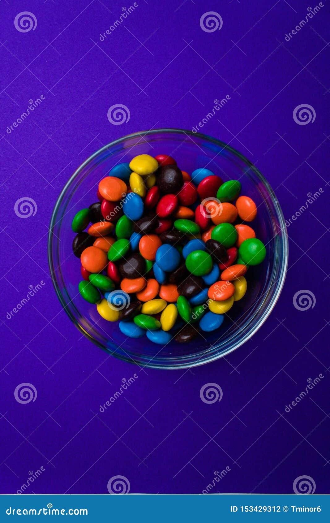 Ciotola riempita di caramella multicolore su un fondo porpora