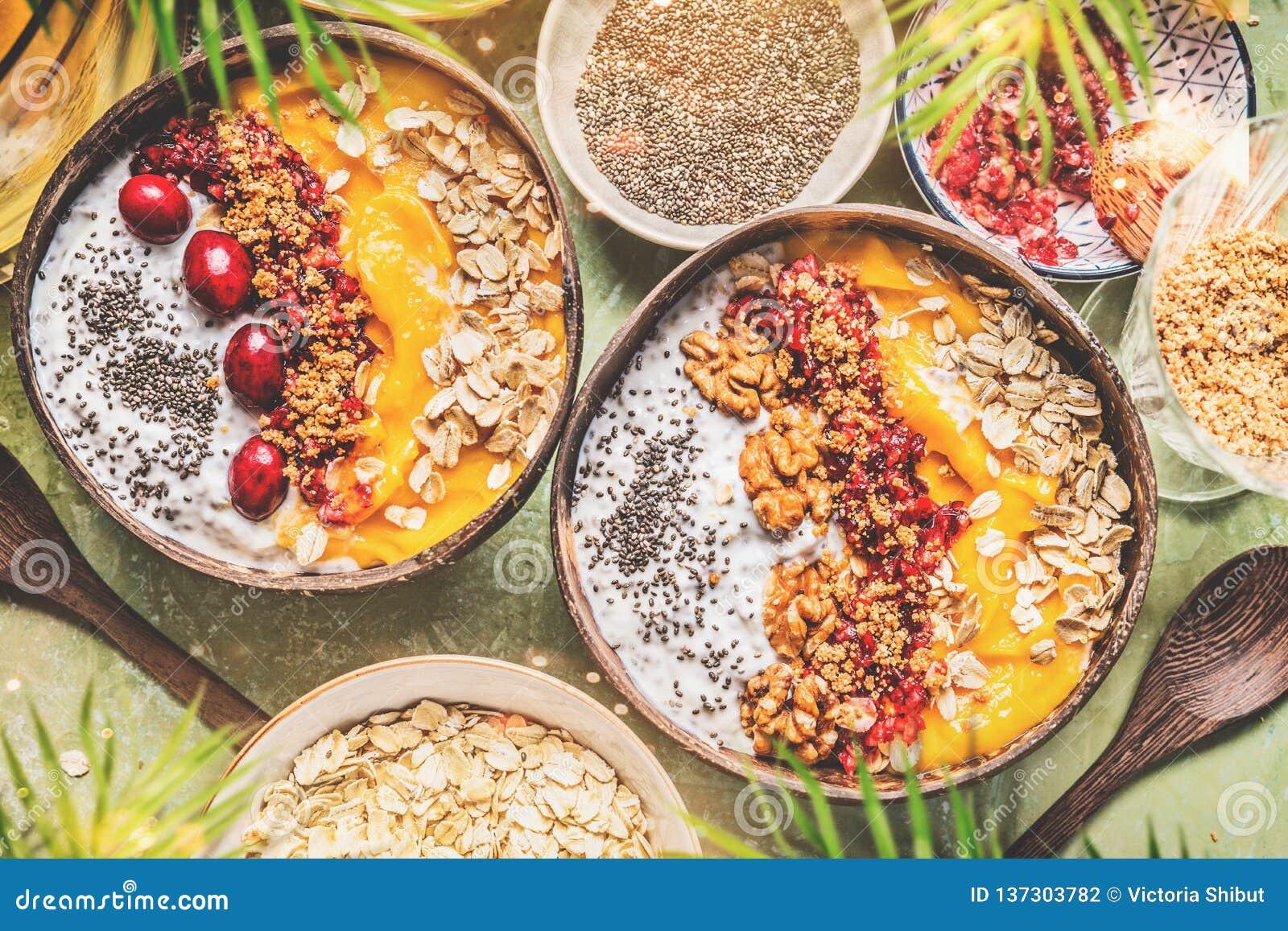 Ciotole del mango del frullato con il budino del yogurt dei semi di chia ed i mirtilli rossi, dadi, farina d avena che completa n